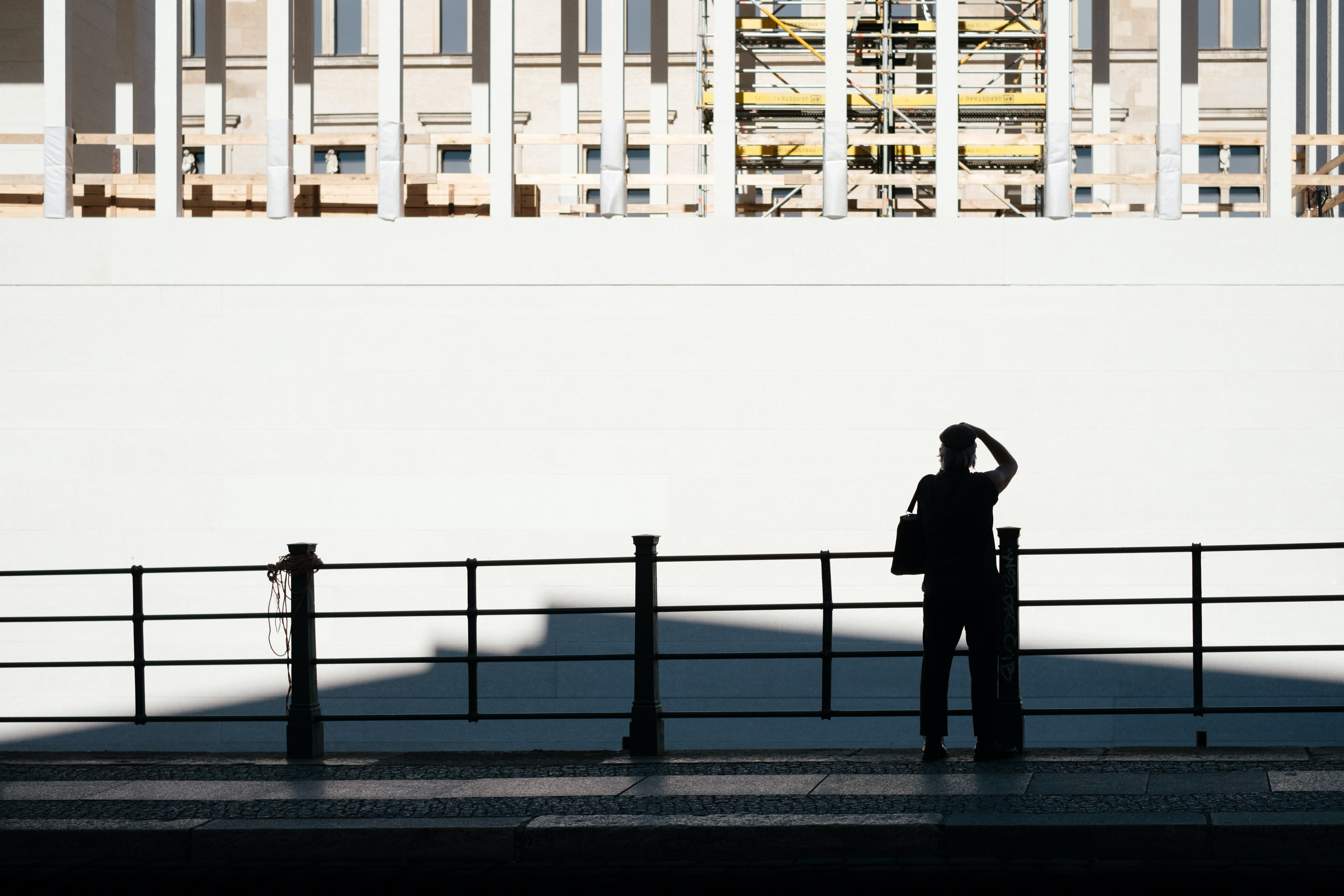 person standing near fence watching white wall