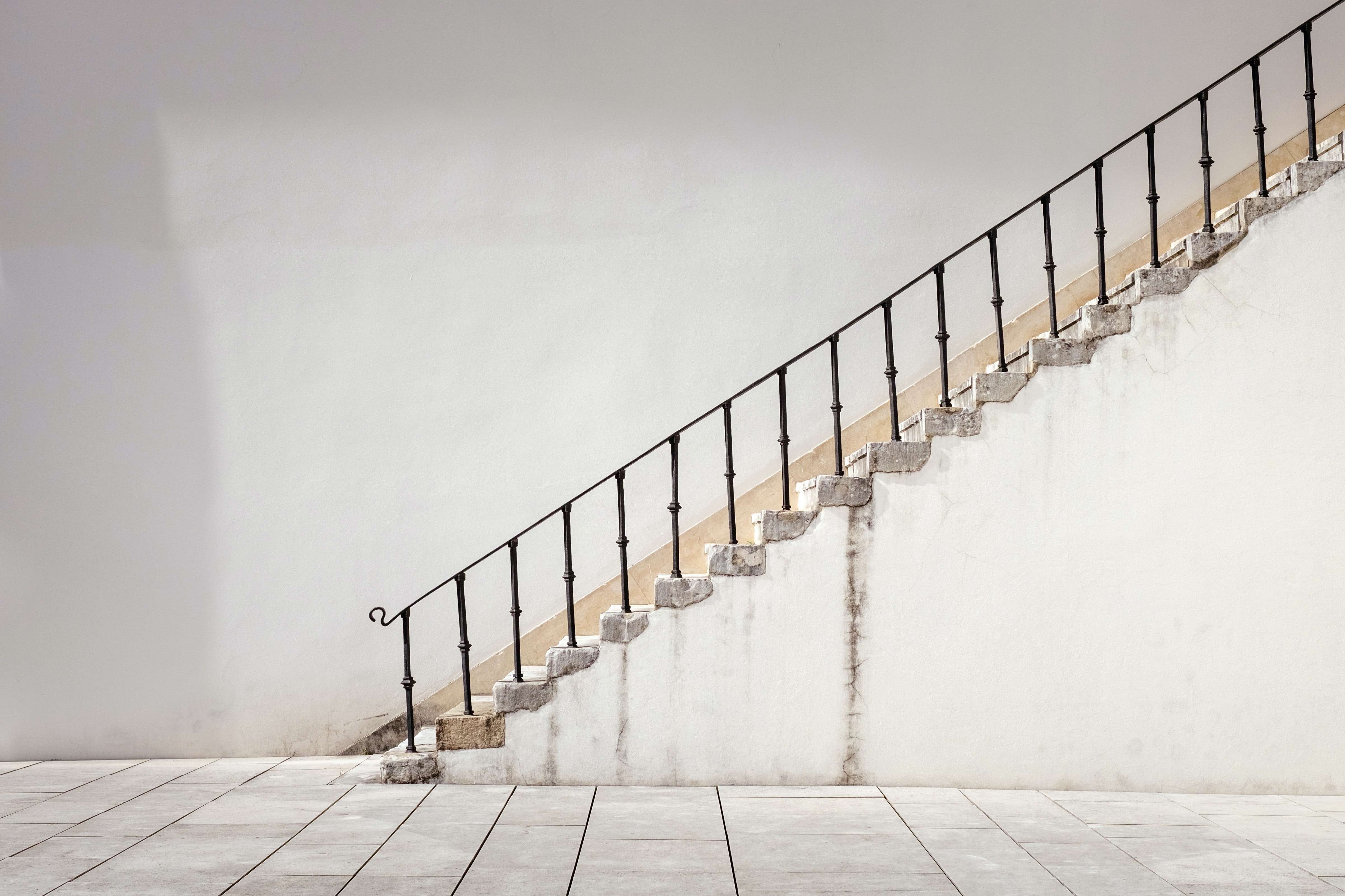 A side shot of old white stairs with a black bannister