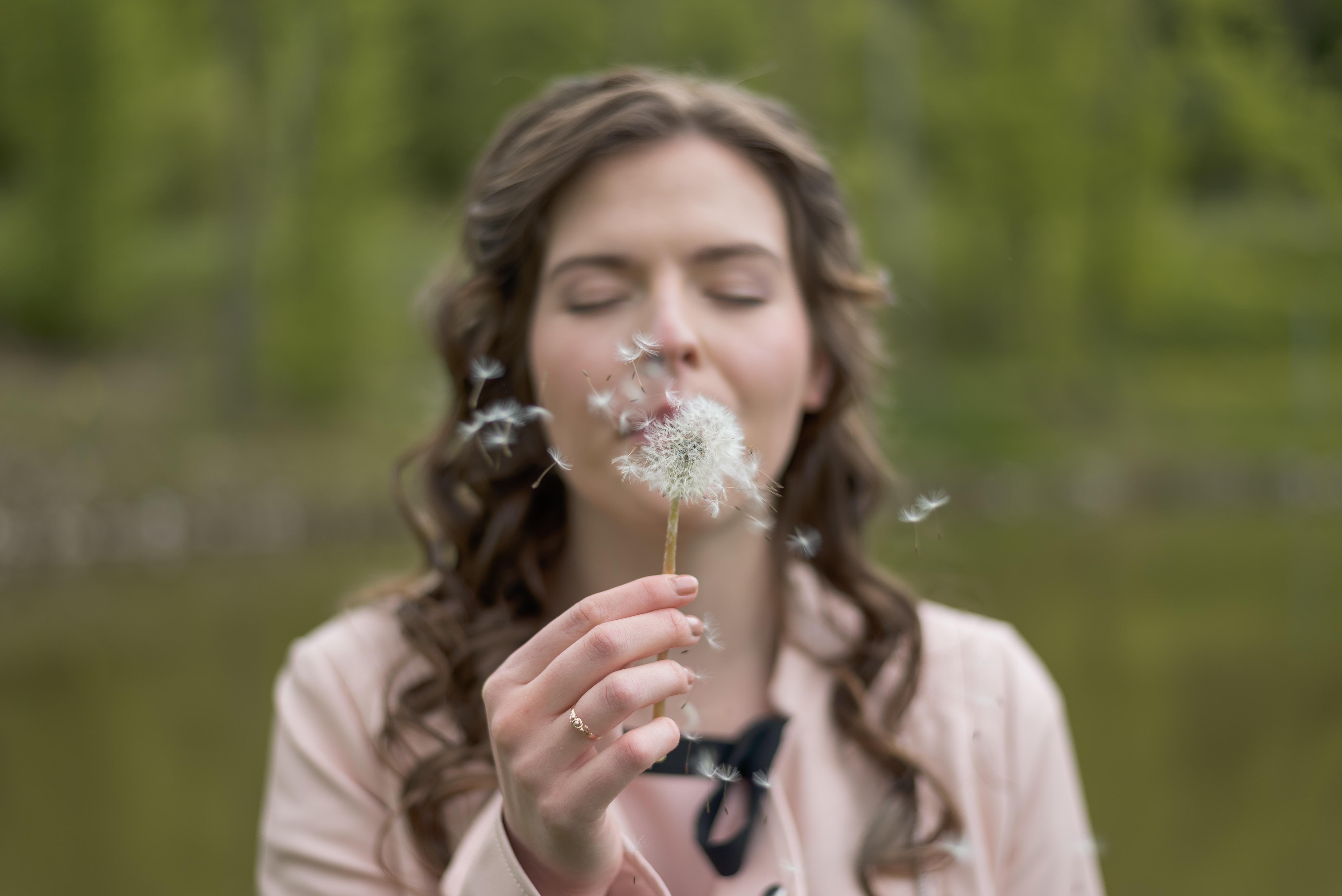 A woman with eyes closed blows seeds from a dandelion against a green background