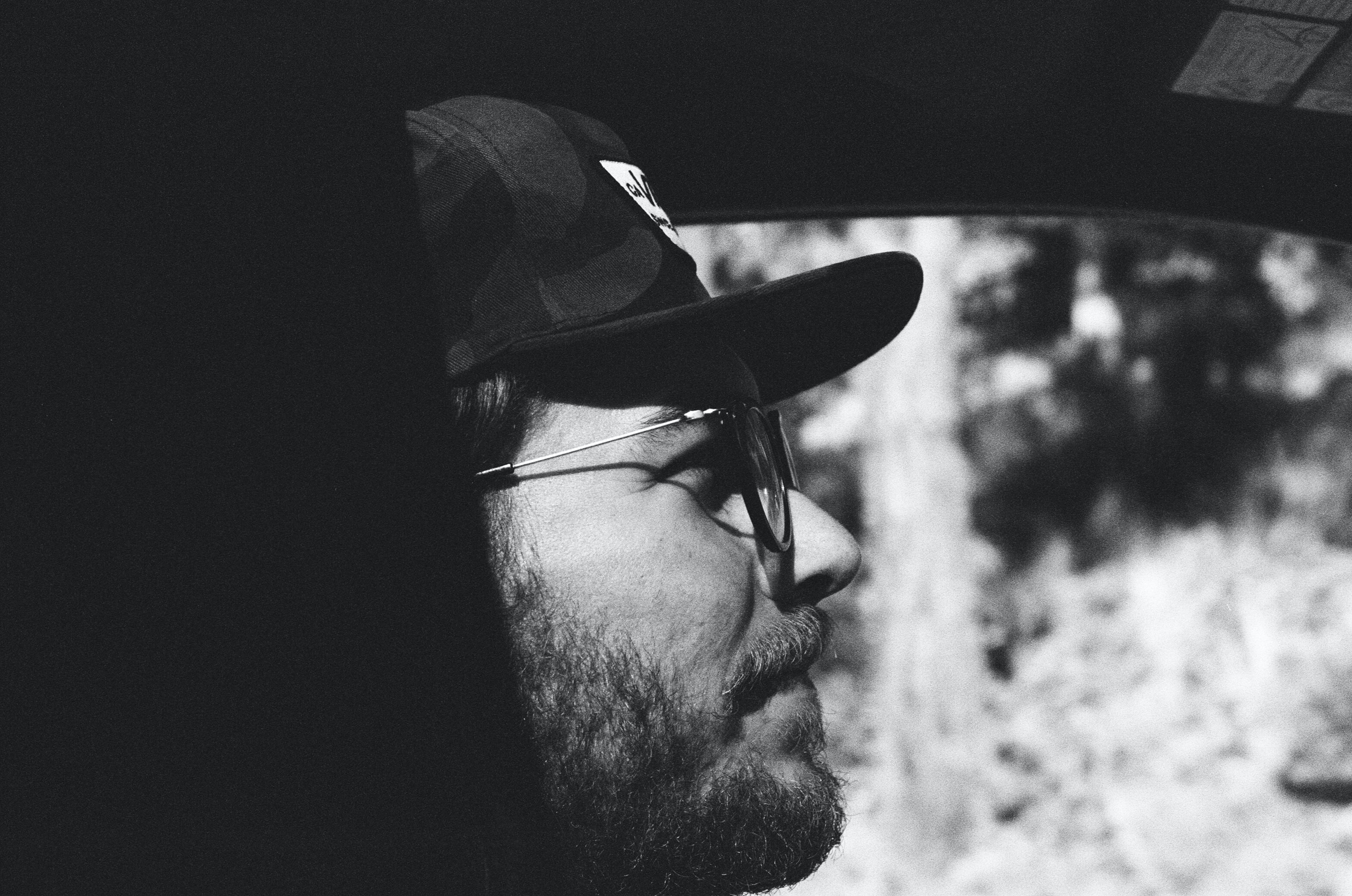 Profile of a man with glasses, a beard, and a hat through a window