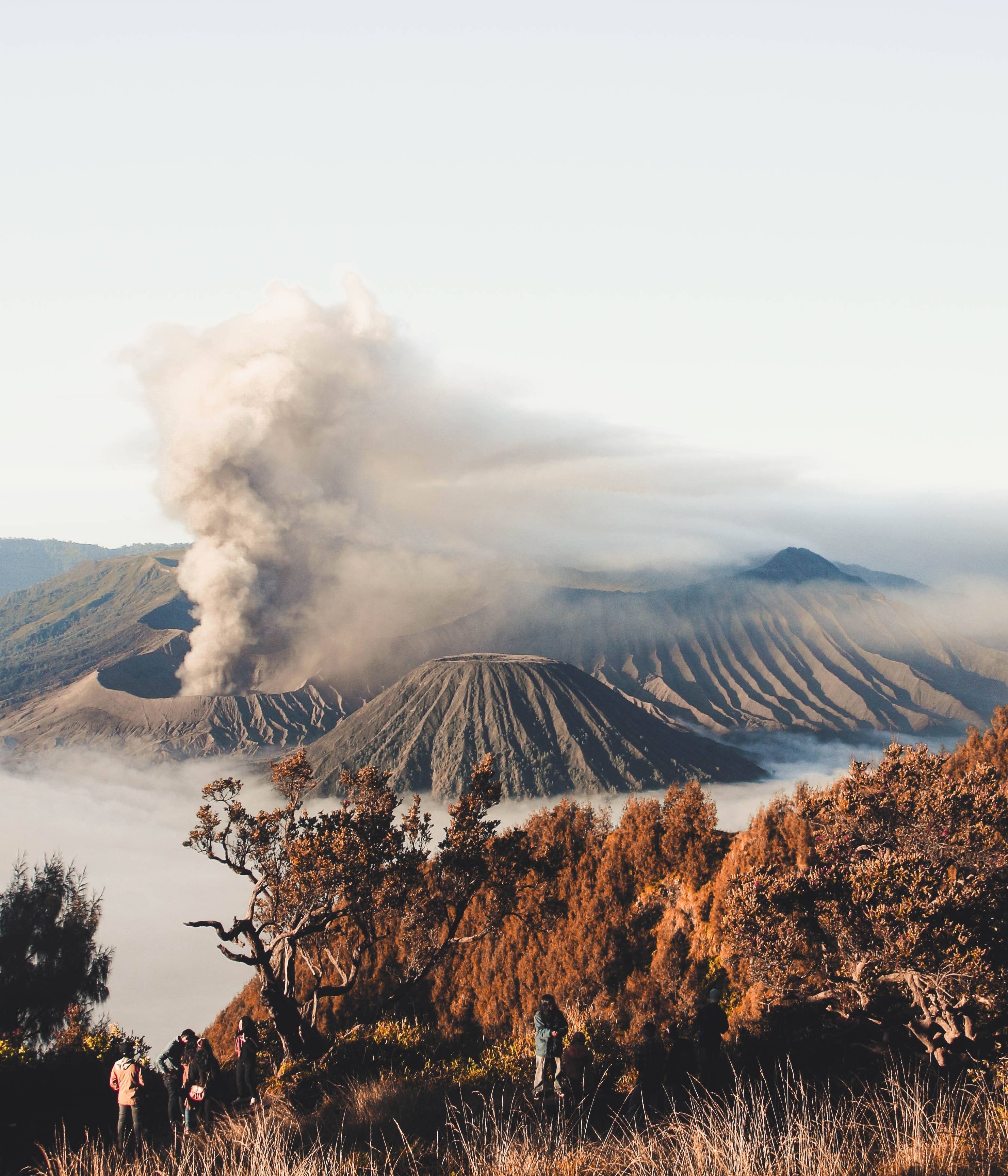 Several people on a mountain slope with a cloud of smoke rising up from a volcano crater in the background
