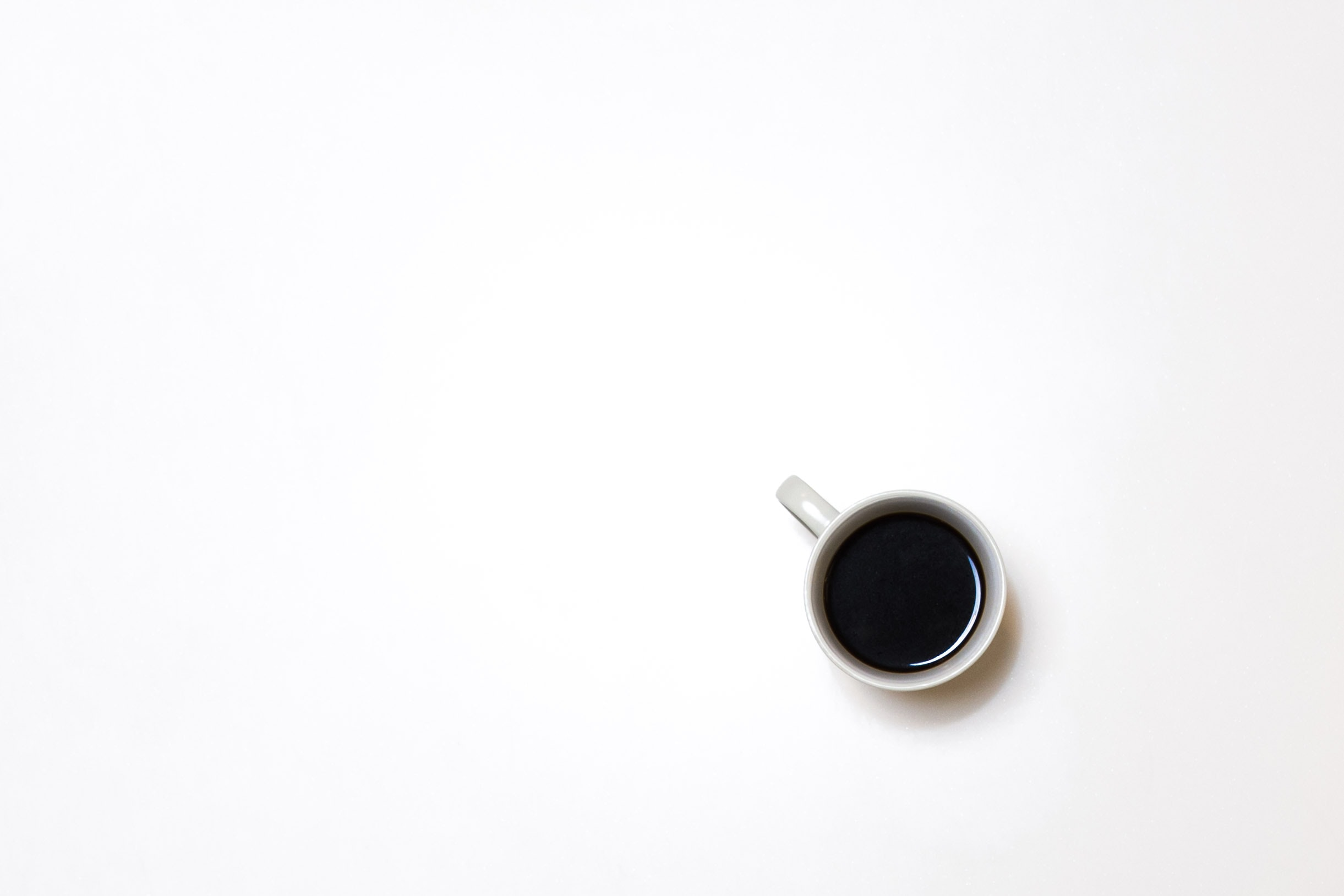 An overhead shot of a cup of coffee on a white surface