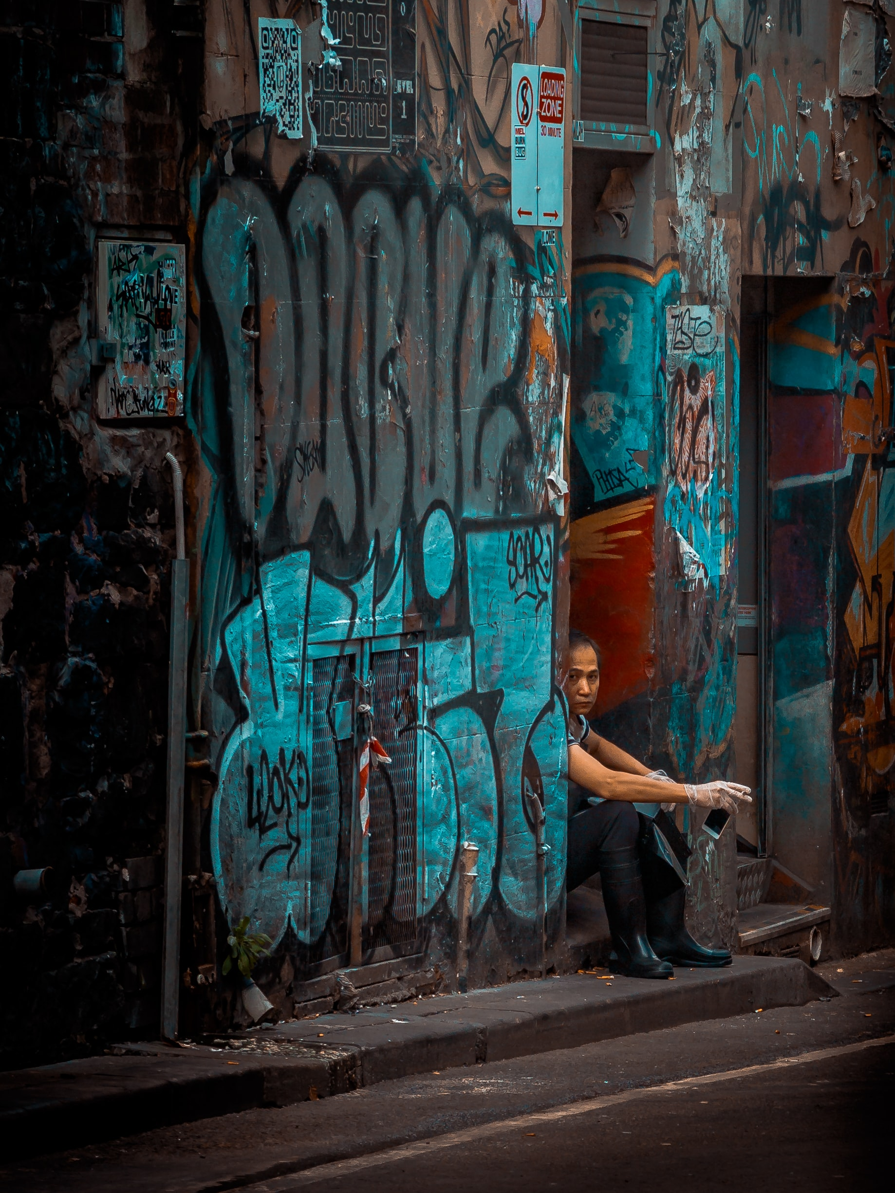 Woman sitting in doorway smoking with blue colored graffiti covered walls in Melbourne alley