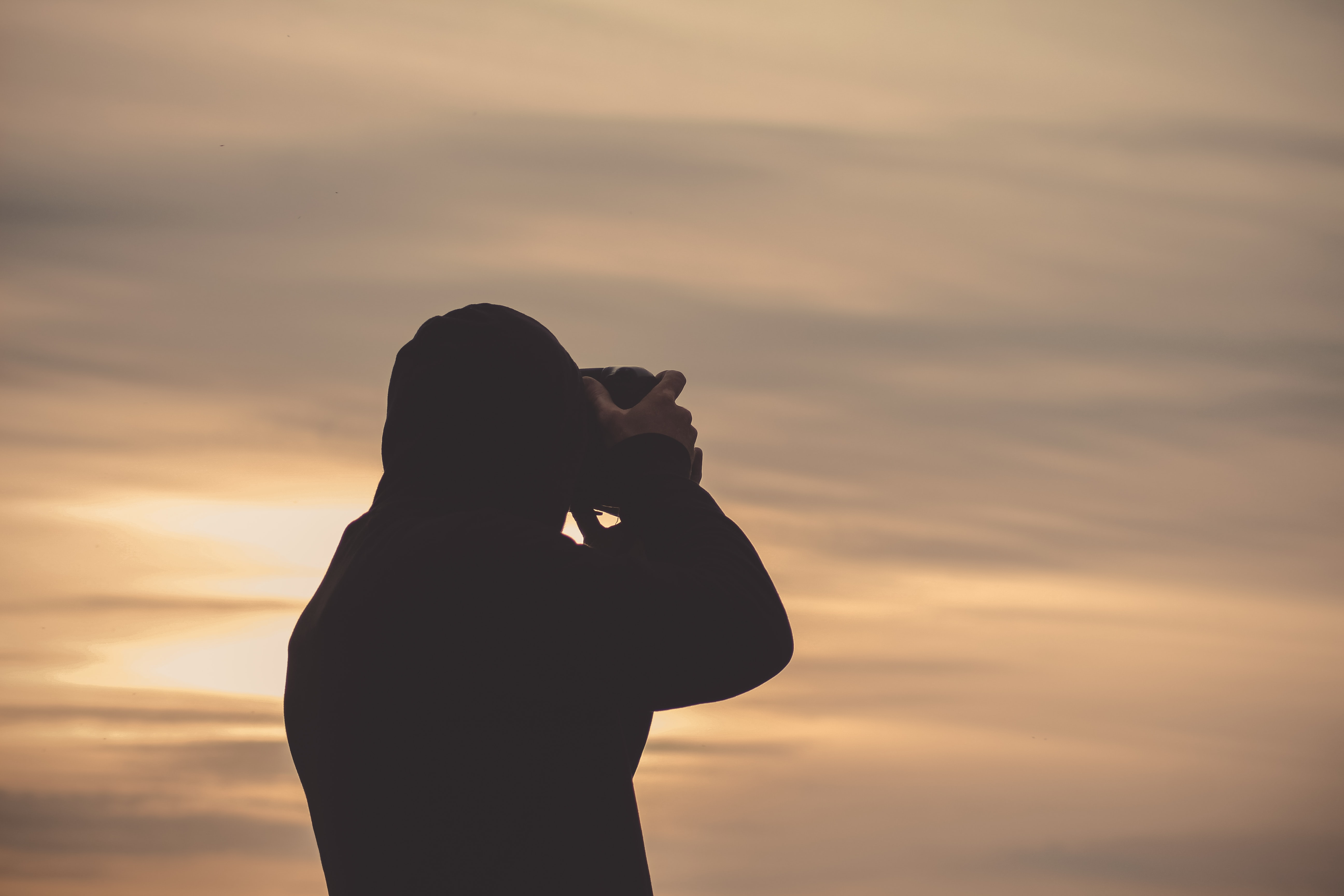 A silhouette of a person taking a photo of the sky