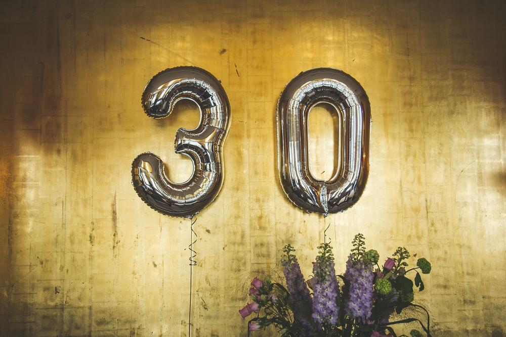 "Large balloons in the shape of the number ""30"" hover over floral bouquets"