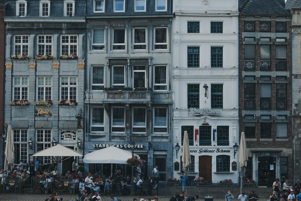white patio umbrellas in front of buildings