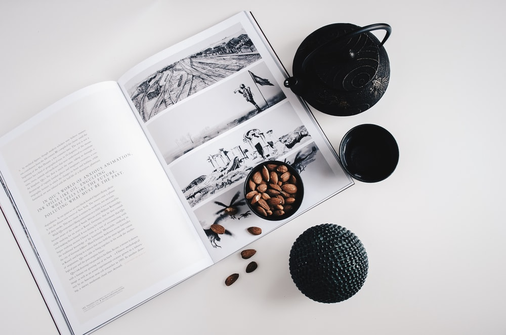 selective color photo of teapot and teacup on book