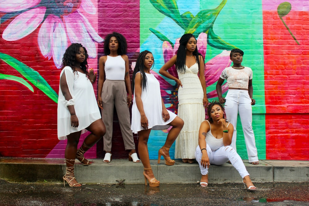 six women wearing white pants posing