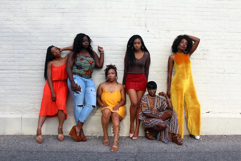 six women leaning on white wall