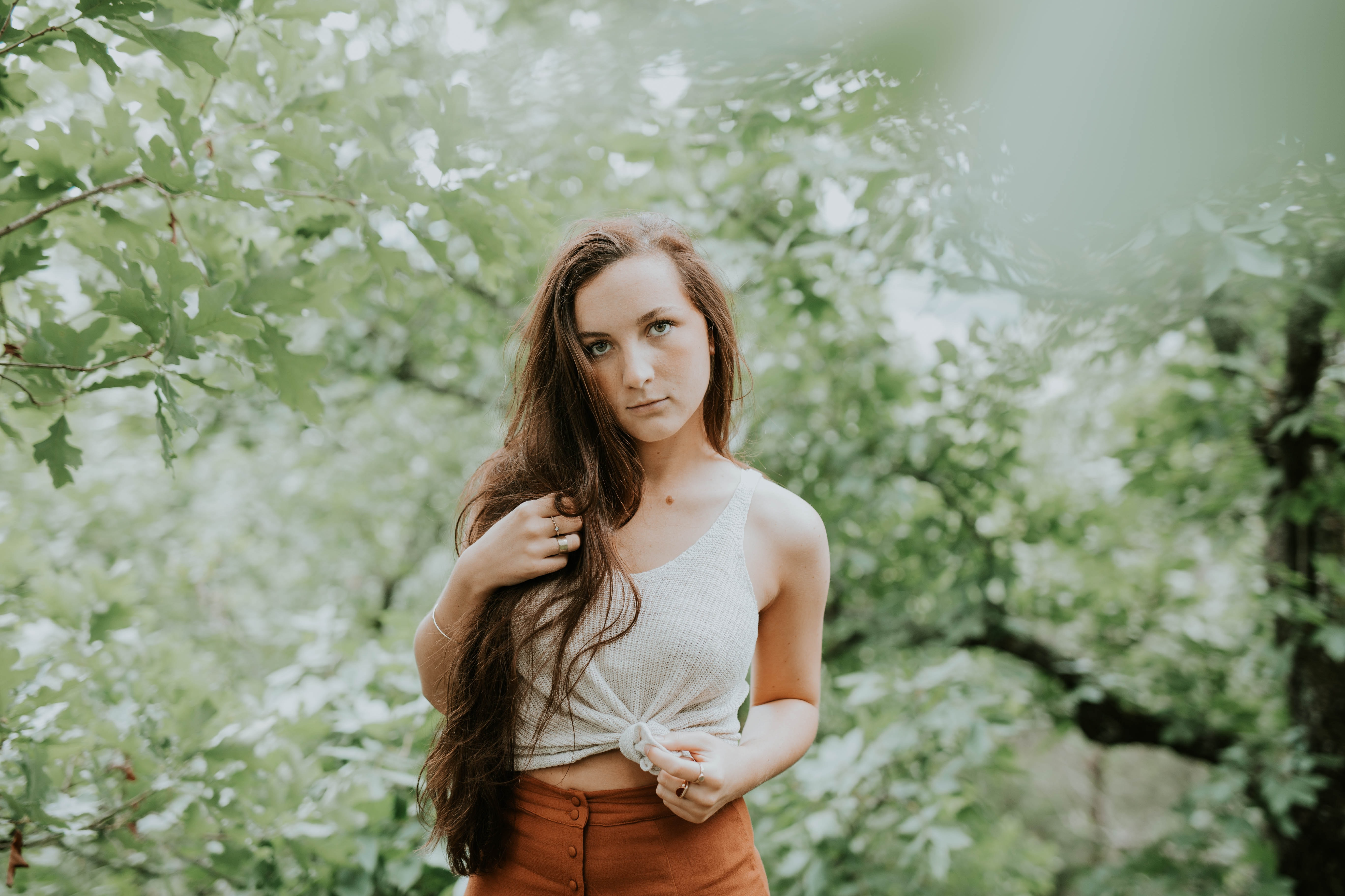 selective focus photography of woman in tank top standing in forest