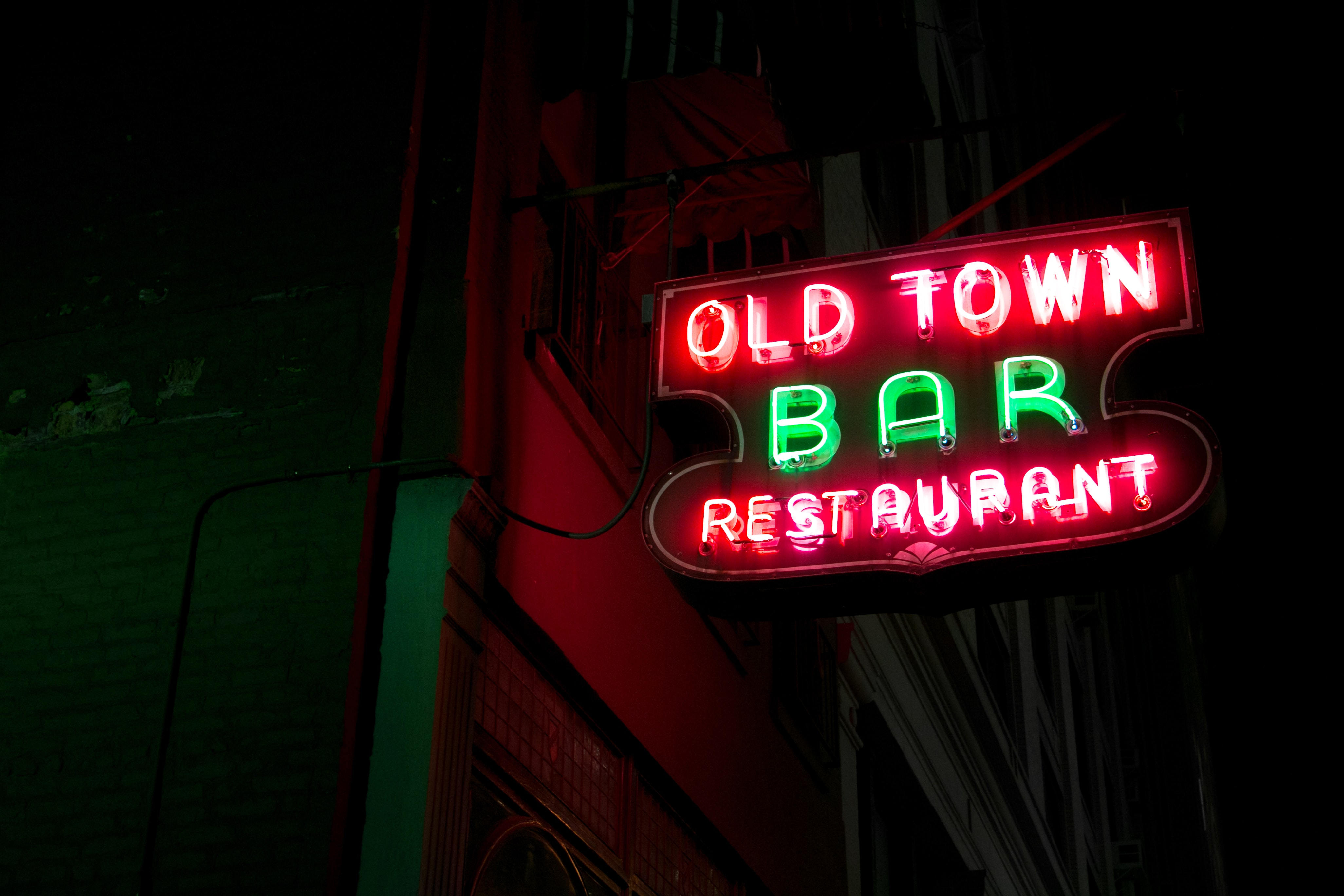 A bright red and green sign in a small town that shines at night.