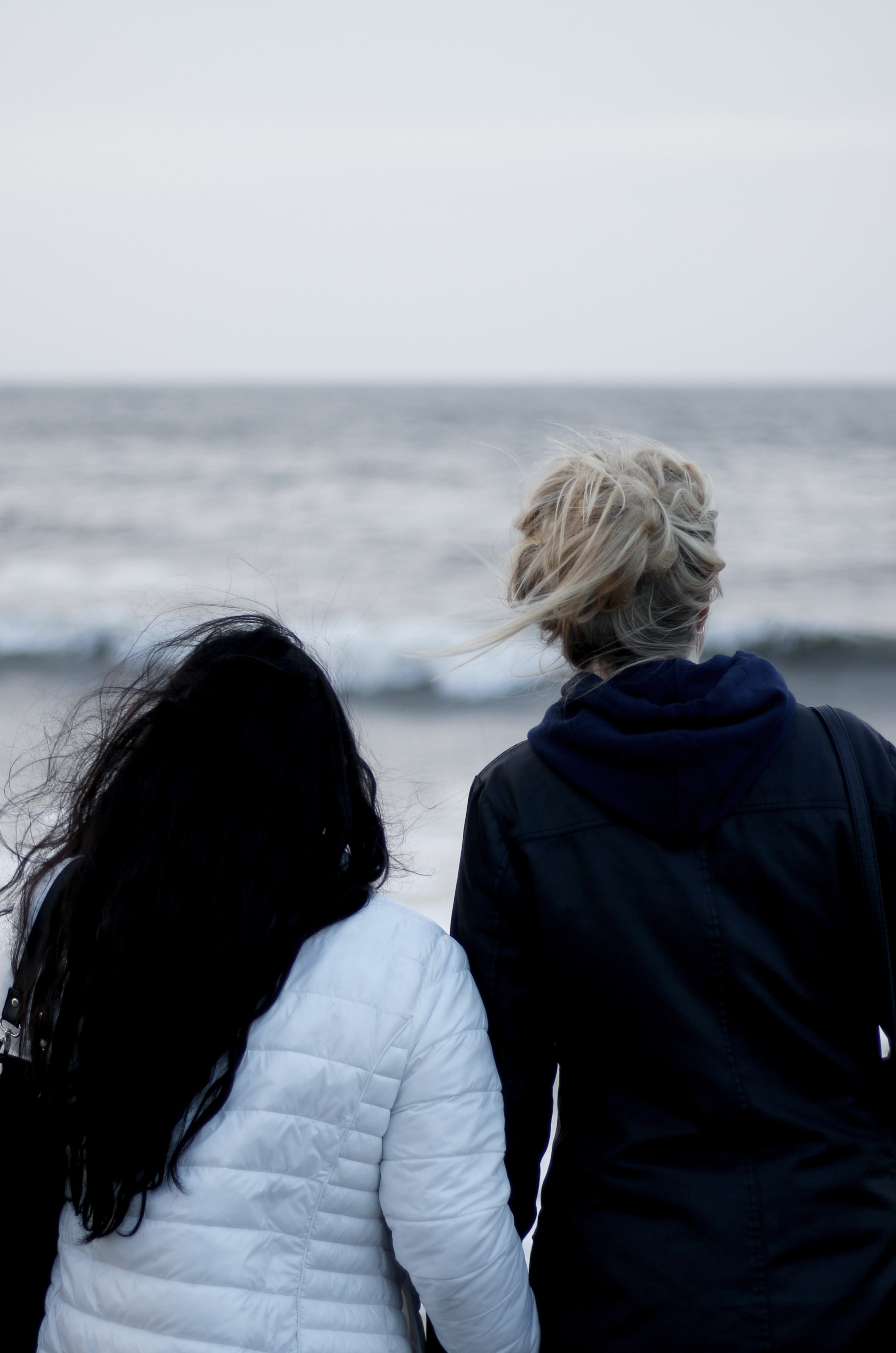 Blonde and brunette stare off into the sea on a cold day