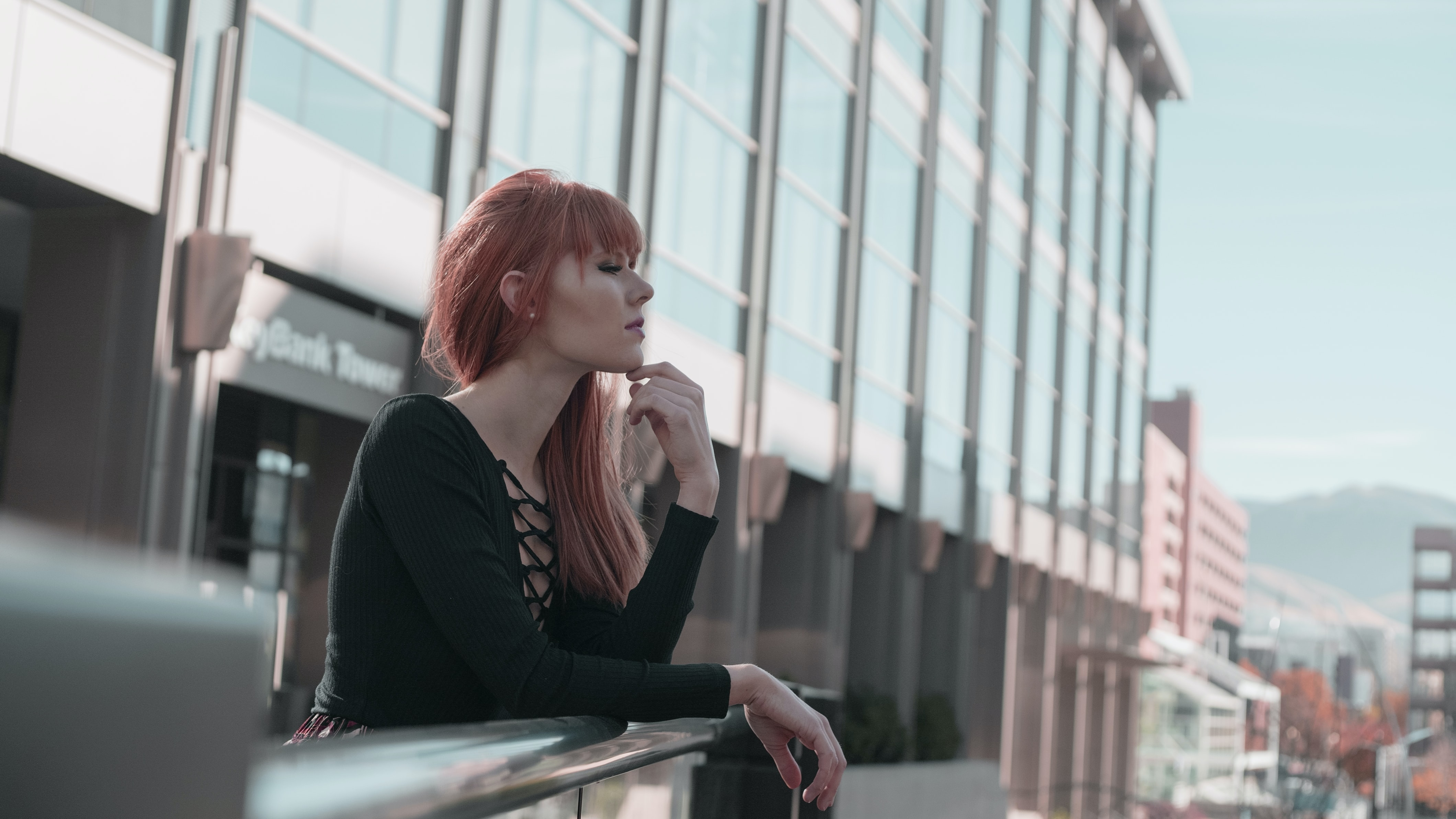 A red-headed woman leaning against a railing