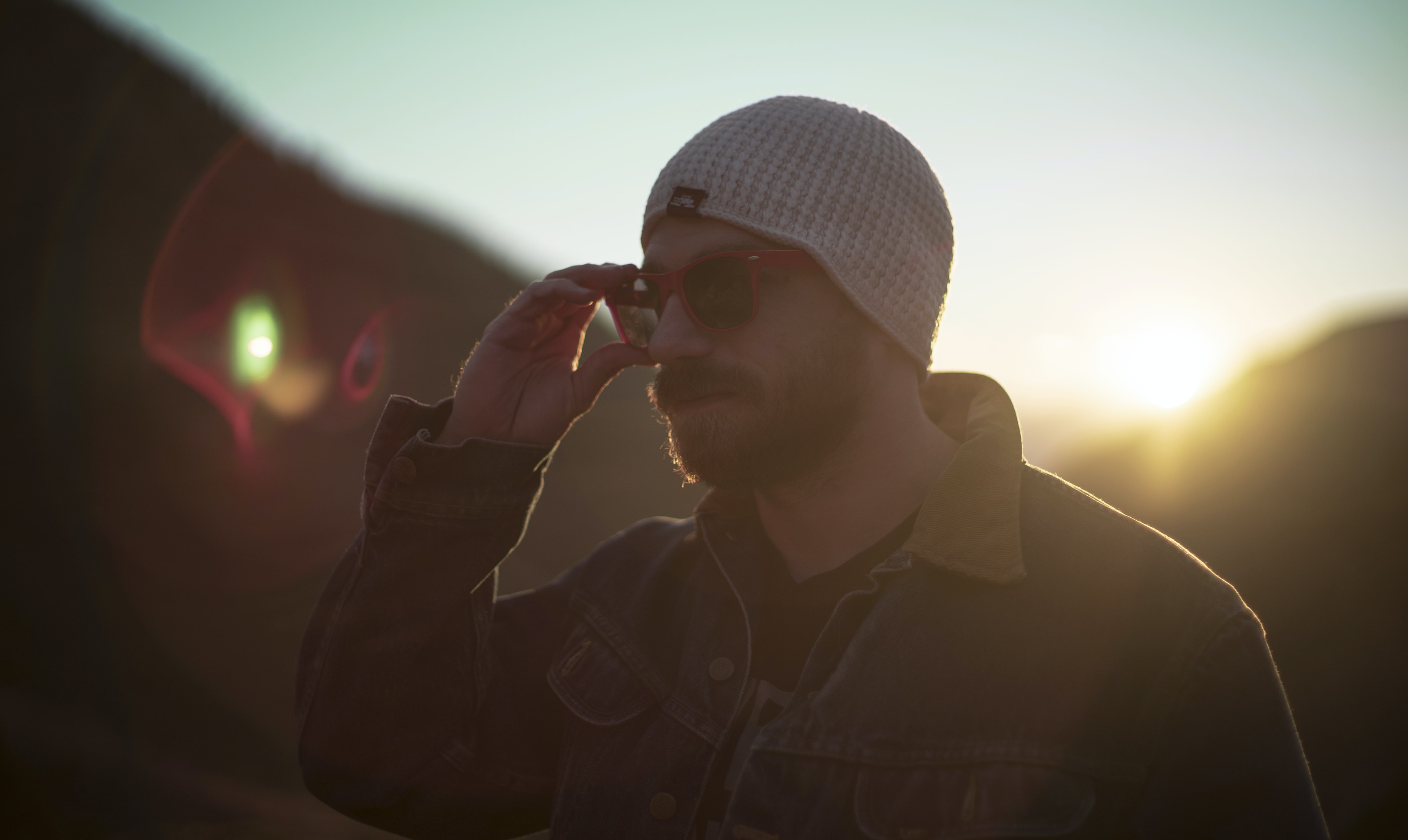 Man with a beard and beanie adjusts sunglasses at dusk