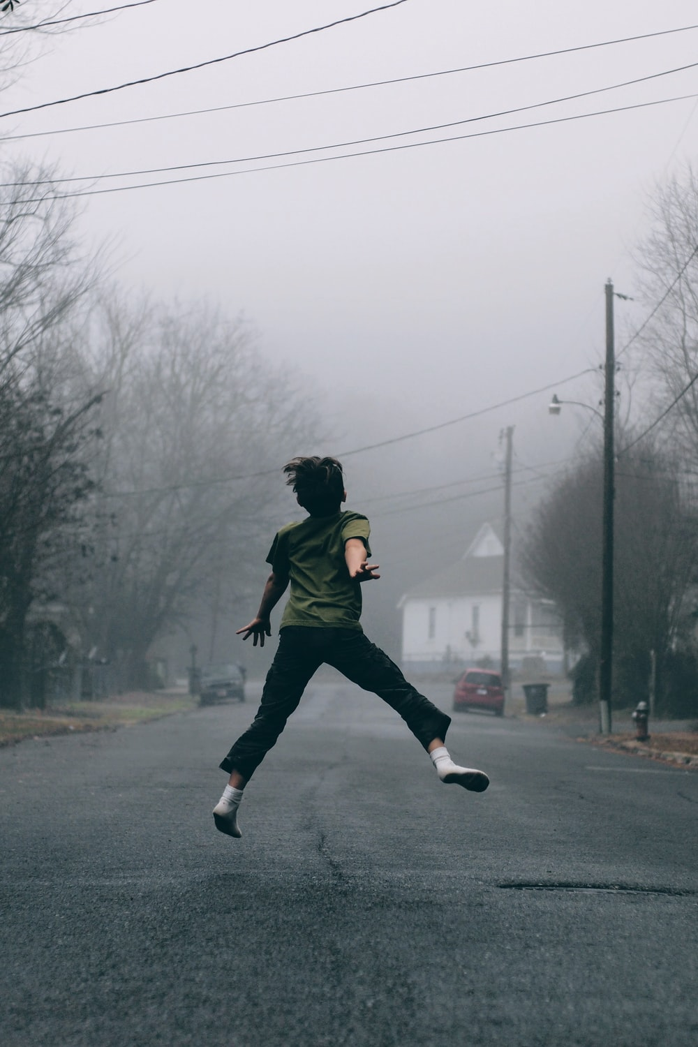 Kid jumps in the middle of the road on a foggy day