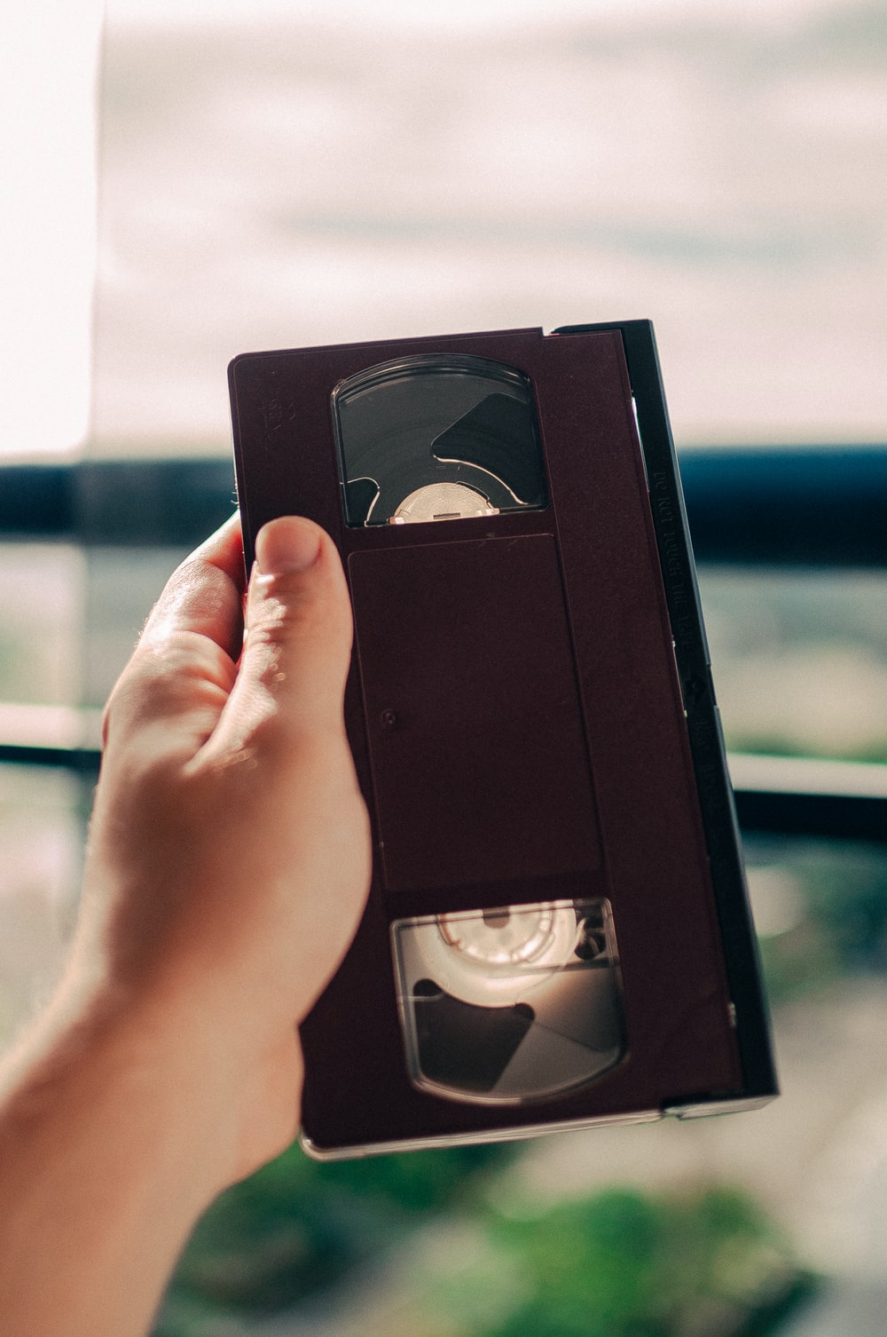 person holding black VHS tape