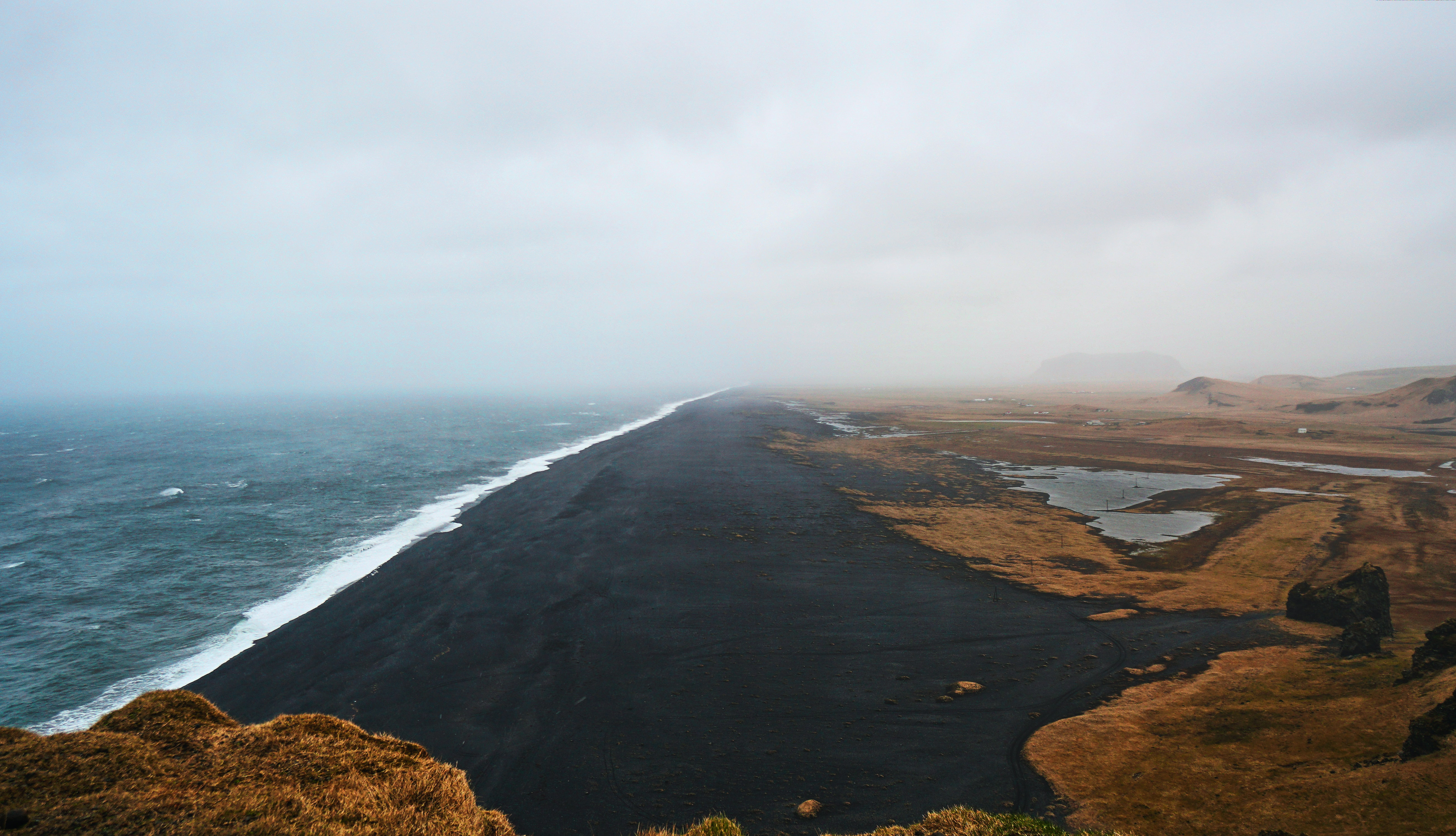 Black sand beach by the ocean on a cloudy day in Iceland