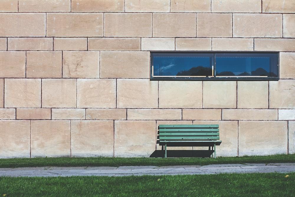 green wooden bench near wall