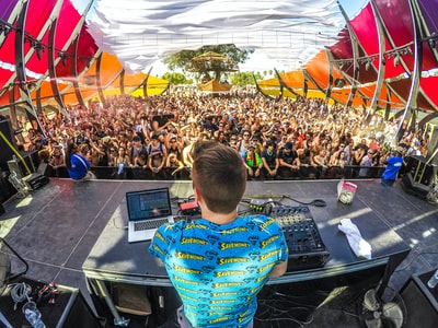 dj on stage in front of audience coachella teams background