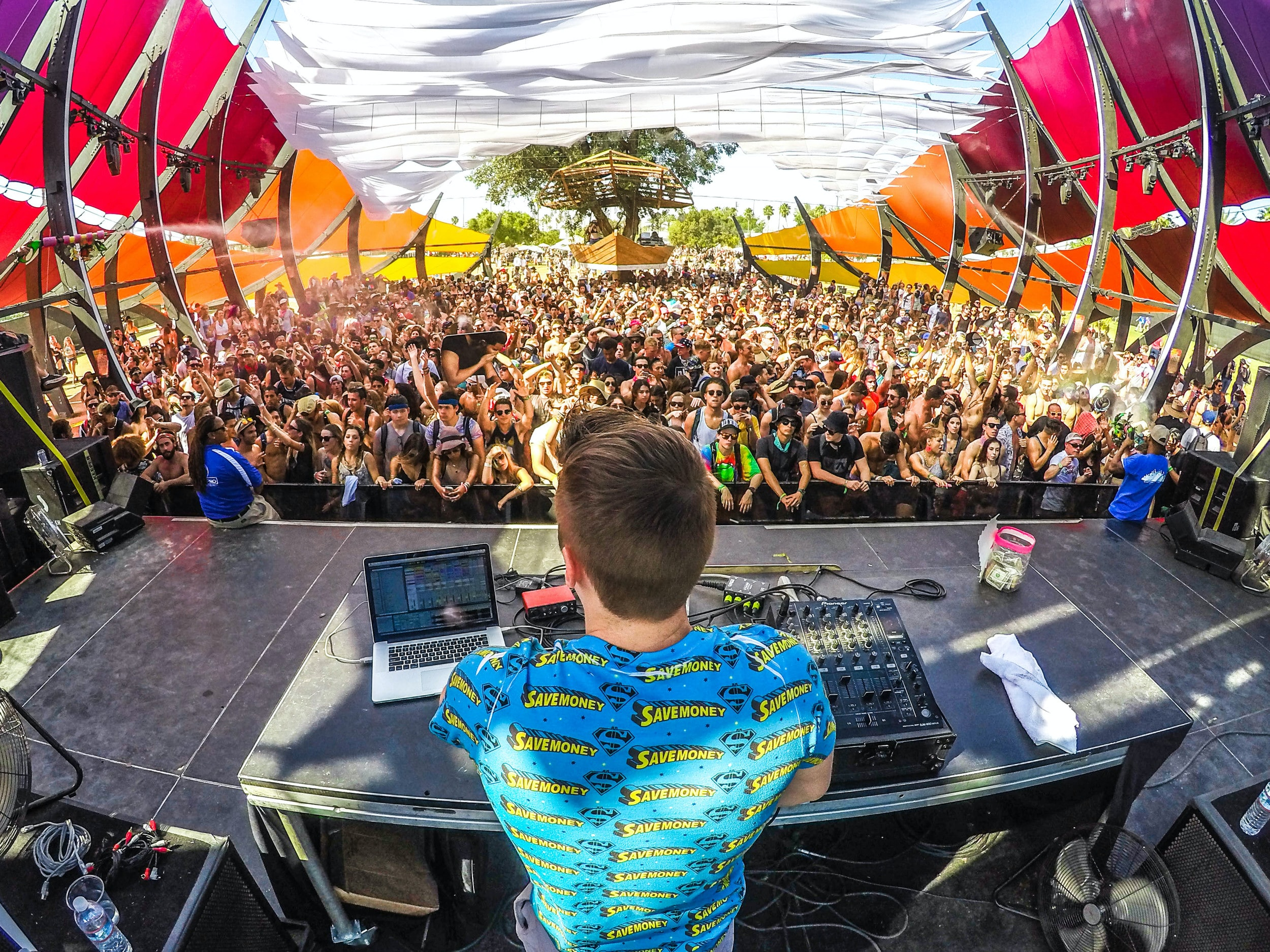 A DJ sitting at a turntable with a laptop nearby during a music festival