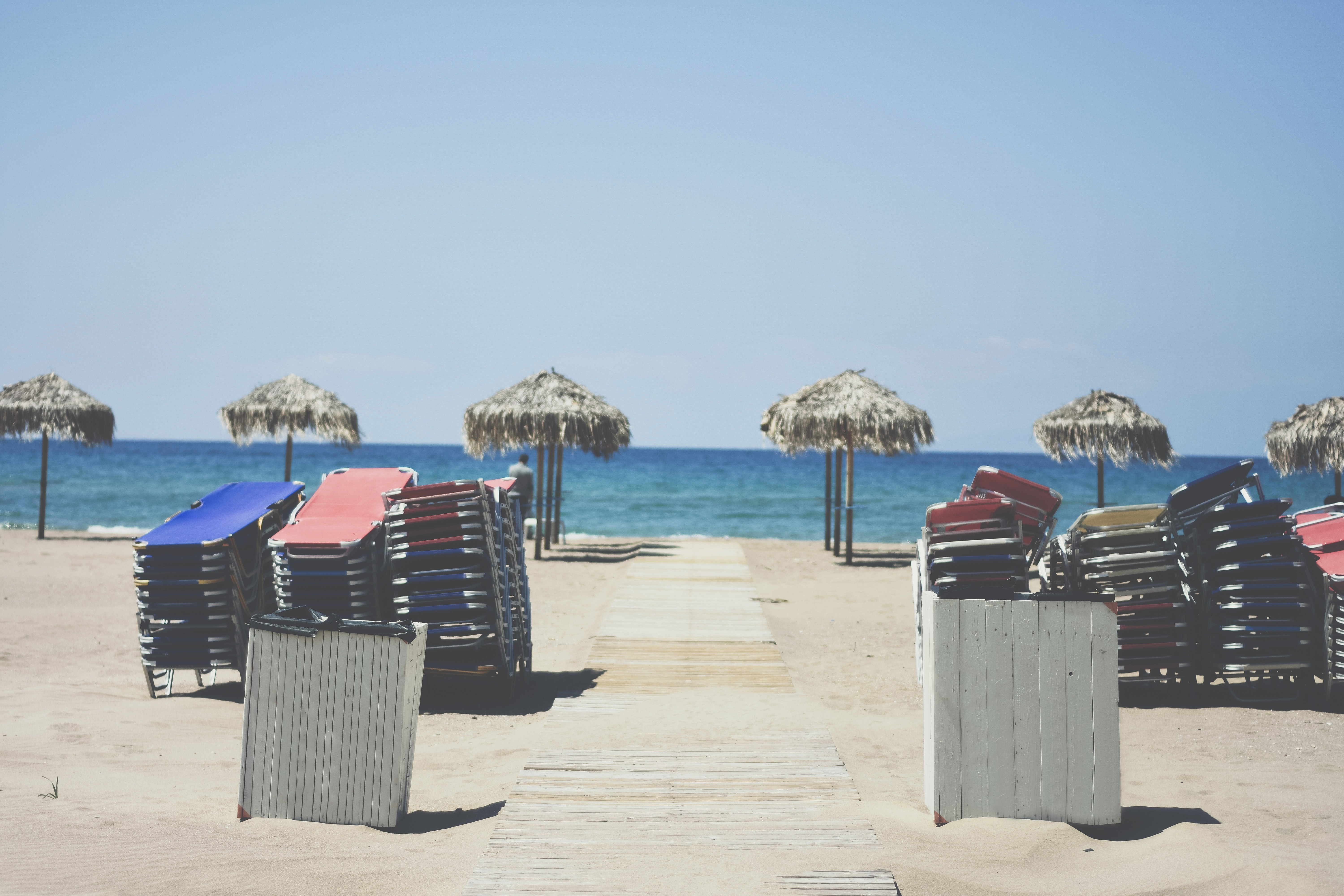 Stacked deck chairs and straw umbrellas on an empty beach
