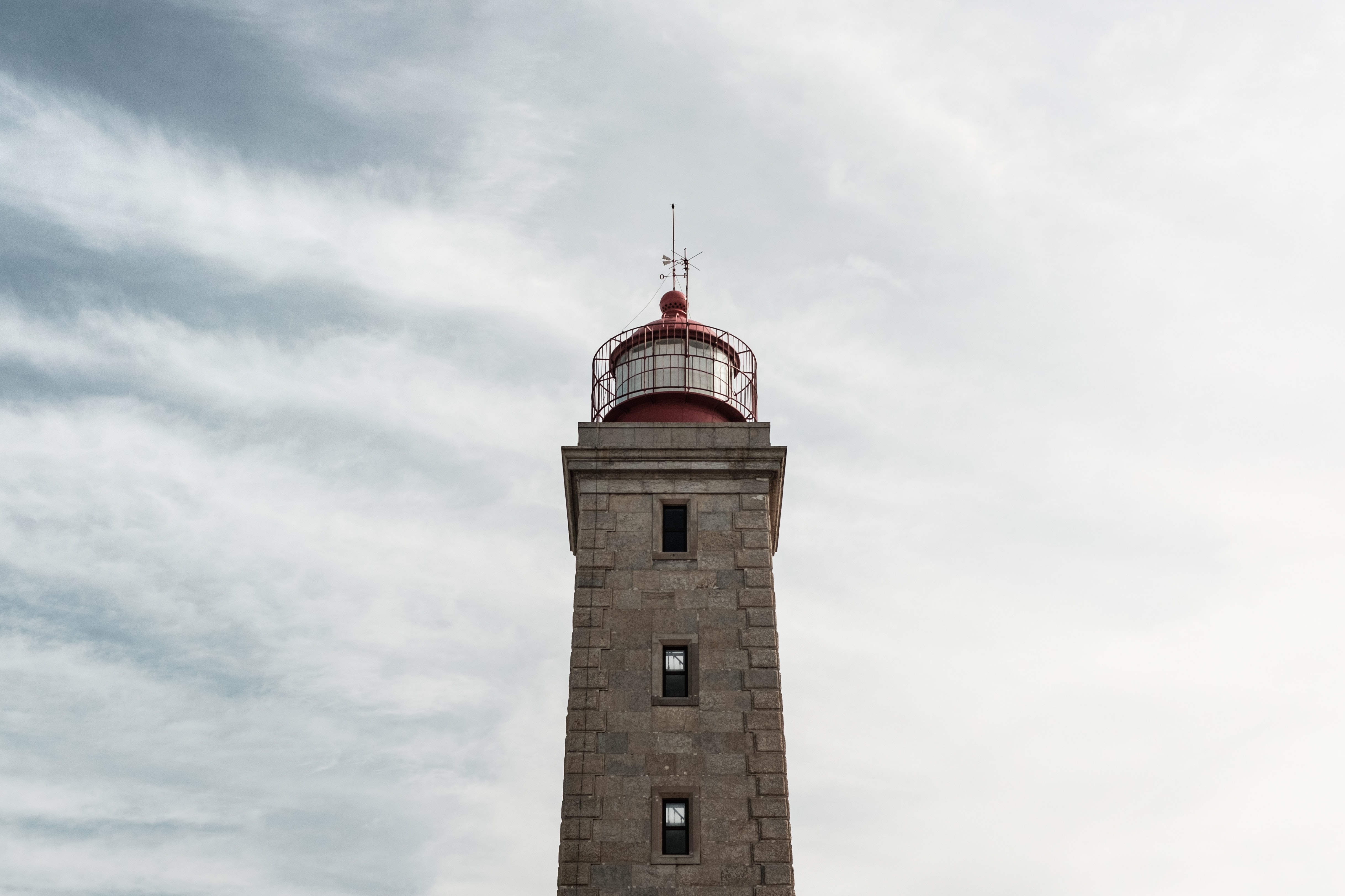 gray and red lighthouse low angle photo