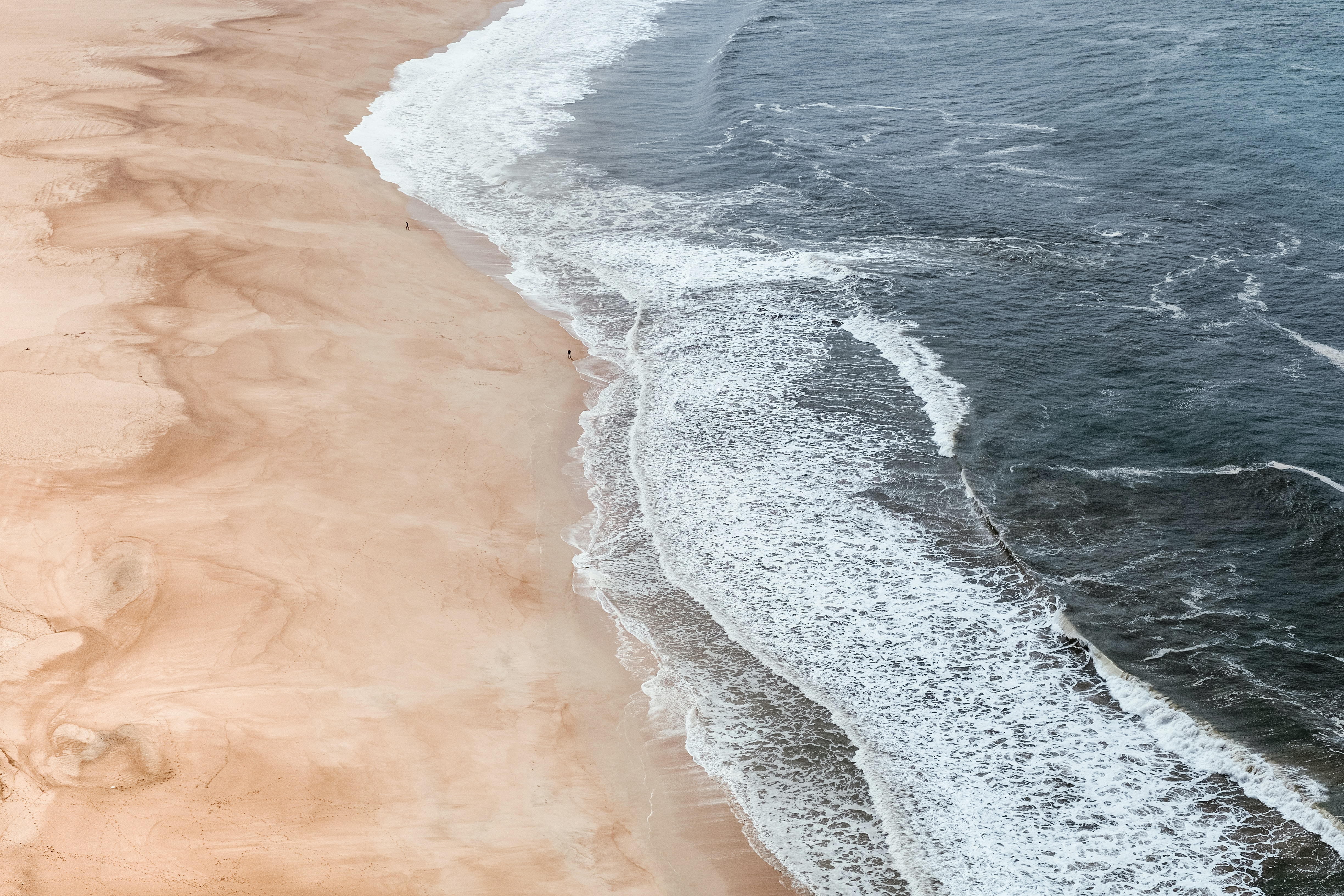 Drone view of the ocean washing on the sand beach coastline at Nazaré