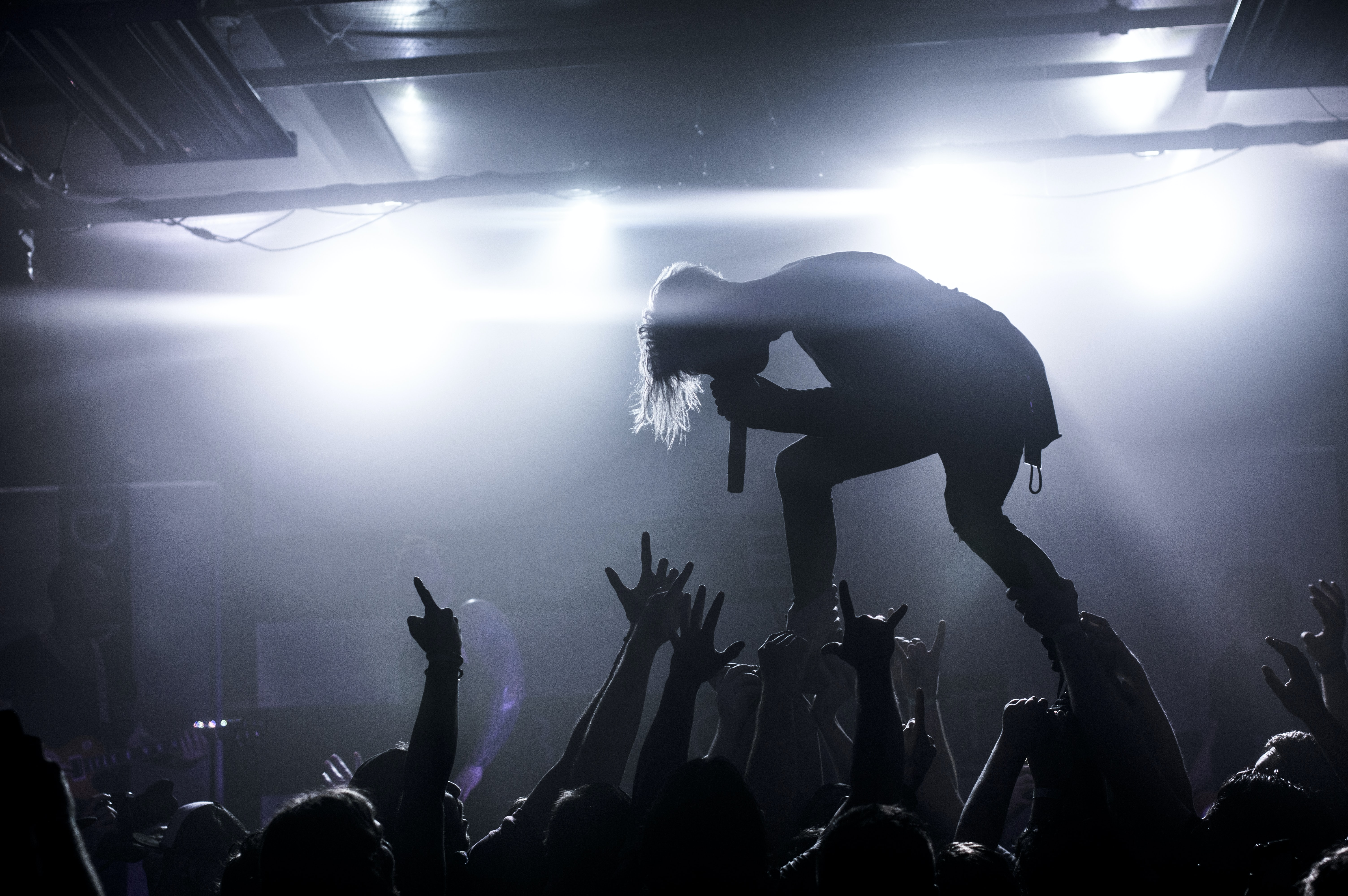 The silhouette of a vocalist held up in the air by the audience during a rock concert