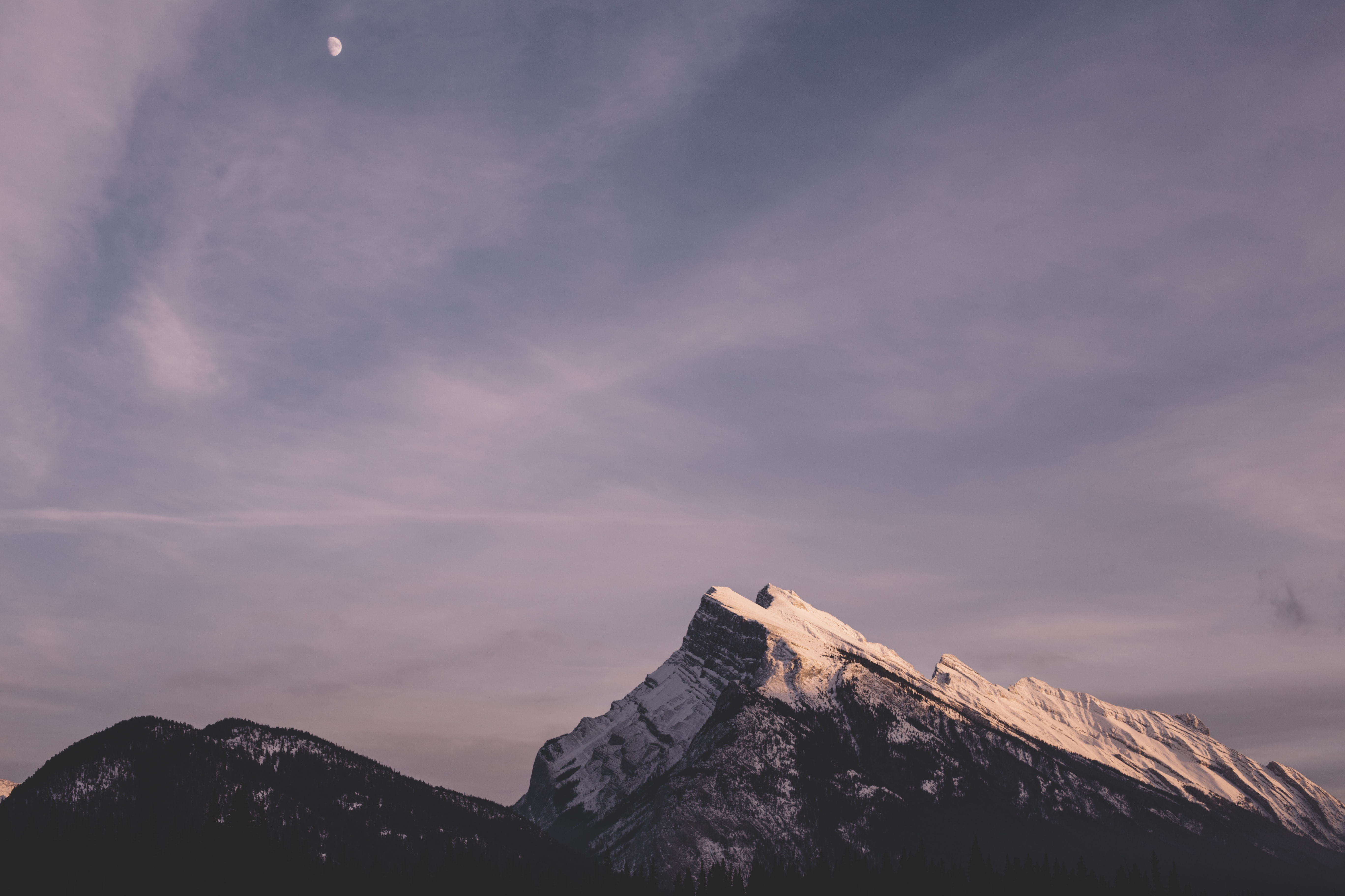 Moon on a cloudy sky over the mountains at Banff
