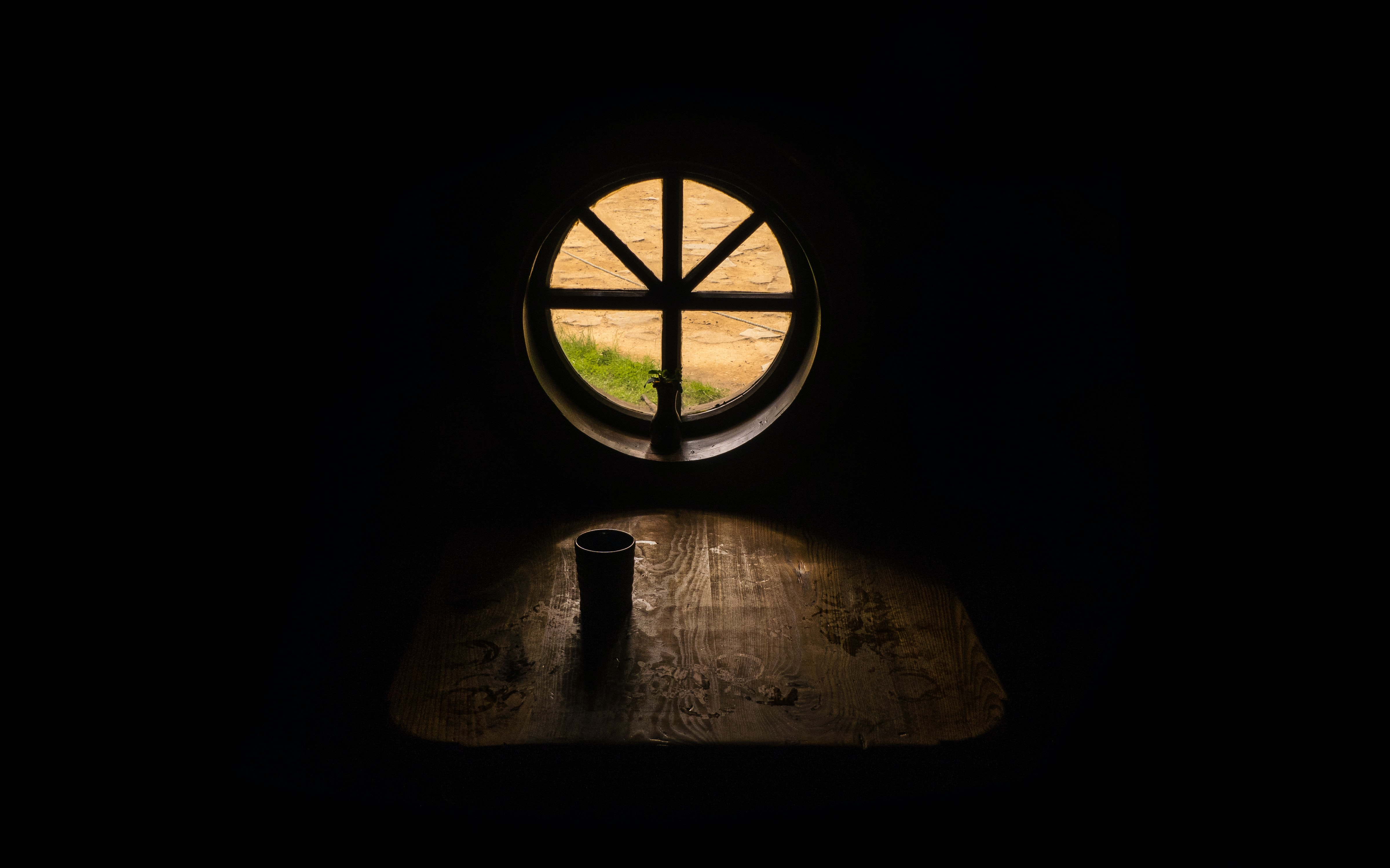Small round window from inside dark room with wooden table and cup, at The Green Dragon Inn