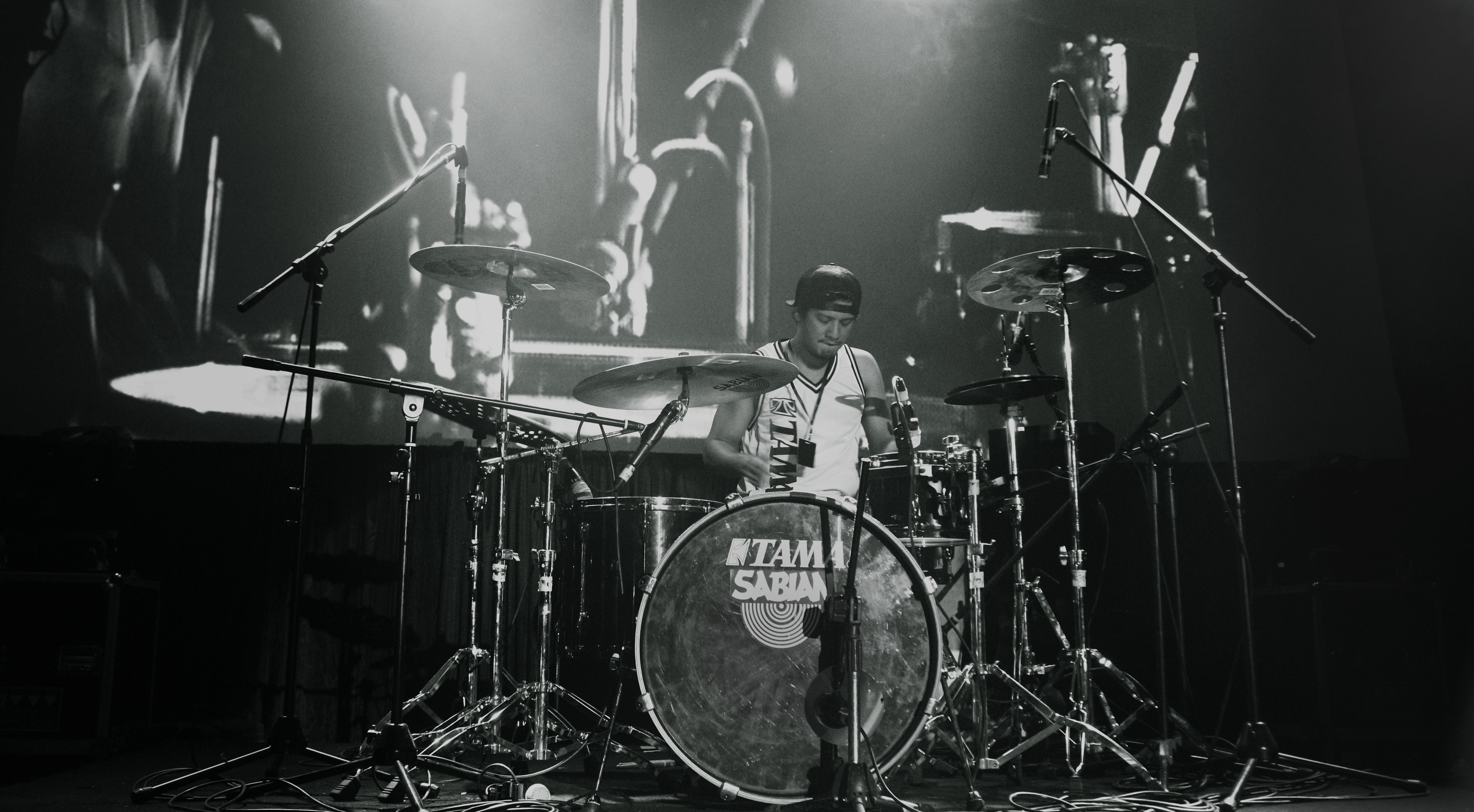 Black and white shot of male drummer performing on stage