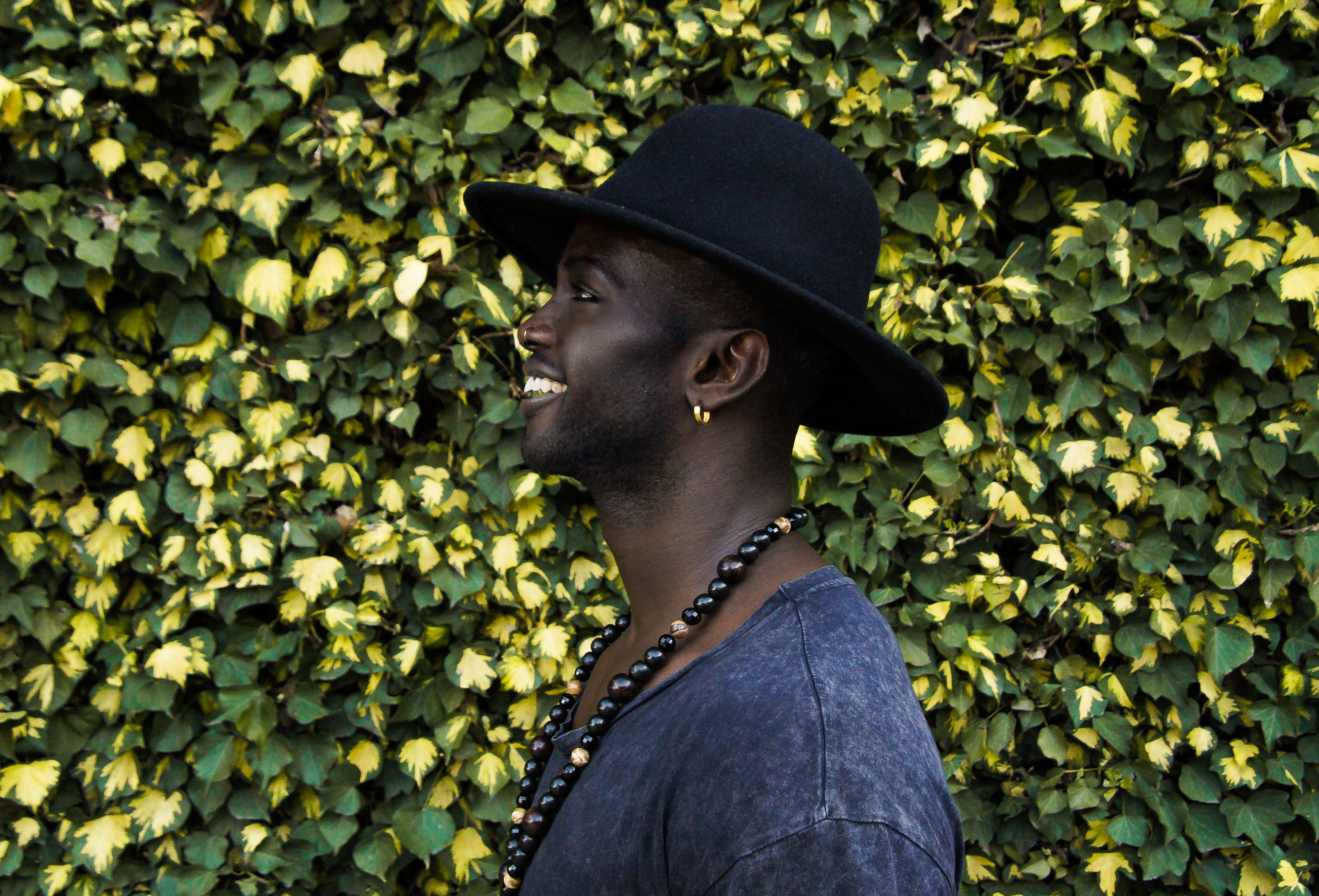 Man in a hat and necklace in front of a tall hedge, smiling to the side