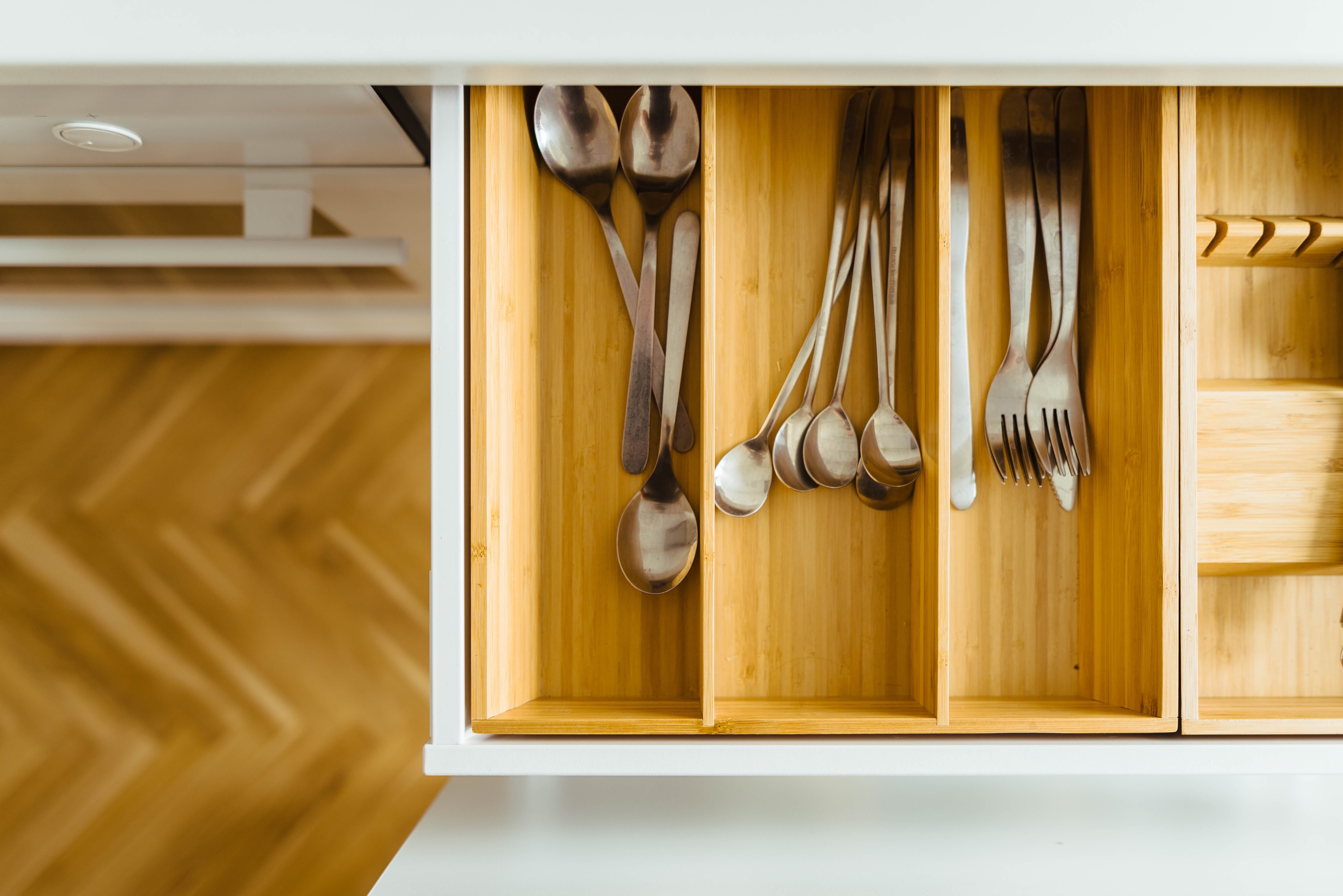 View from above of wooden utensil drawer above wooden floor in kitchen with white cabinets