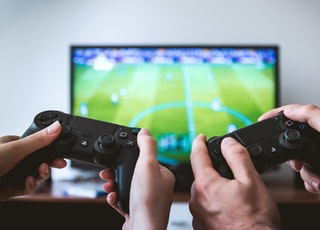 two people playing Sony PS4 game console