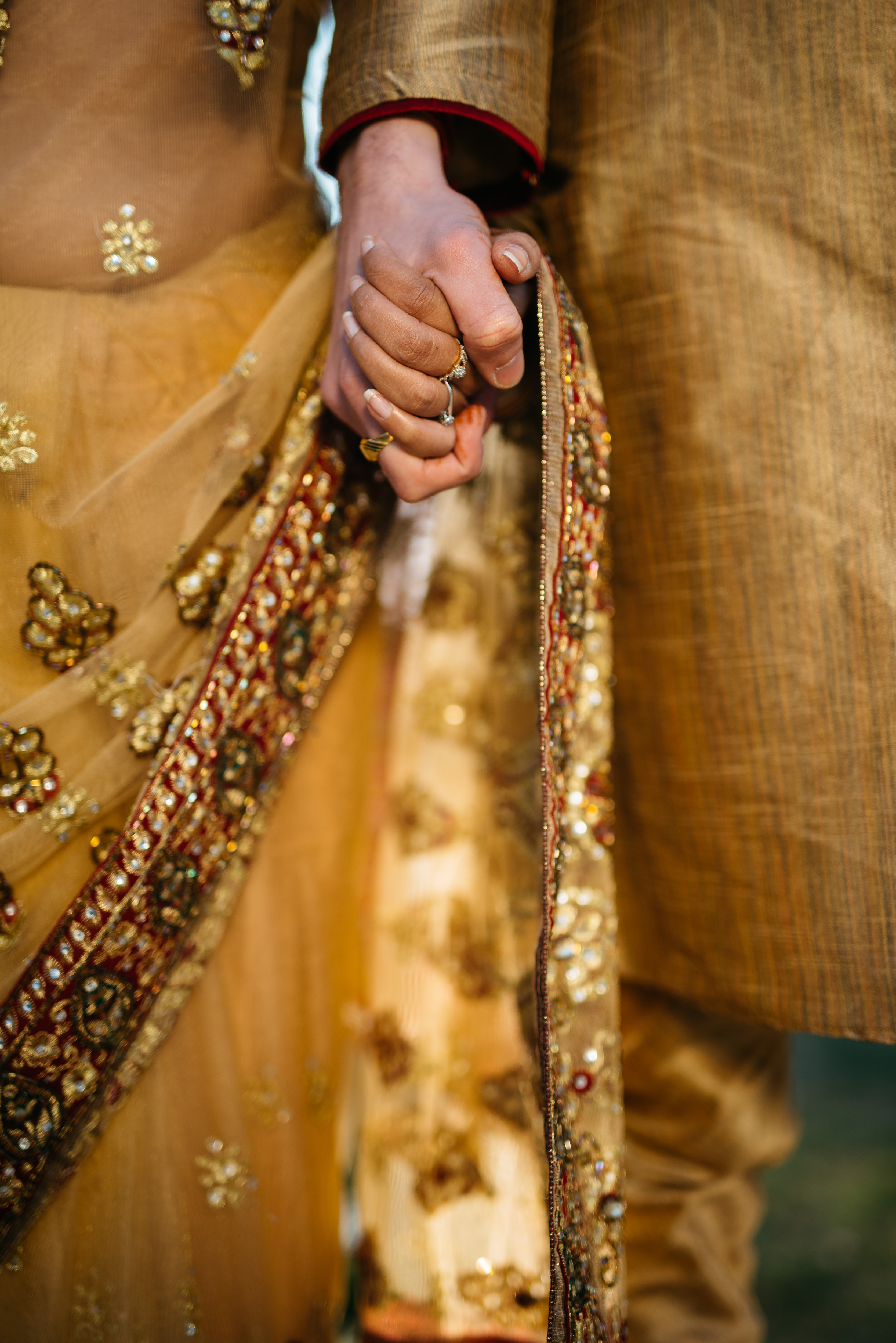 Couple in traditional garb holds hands at wedding