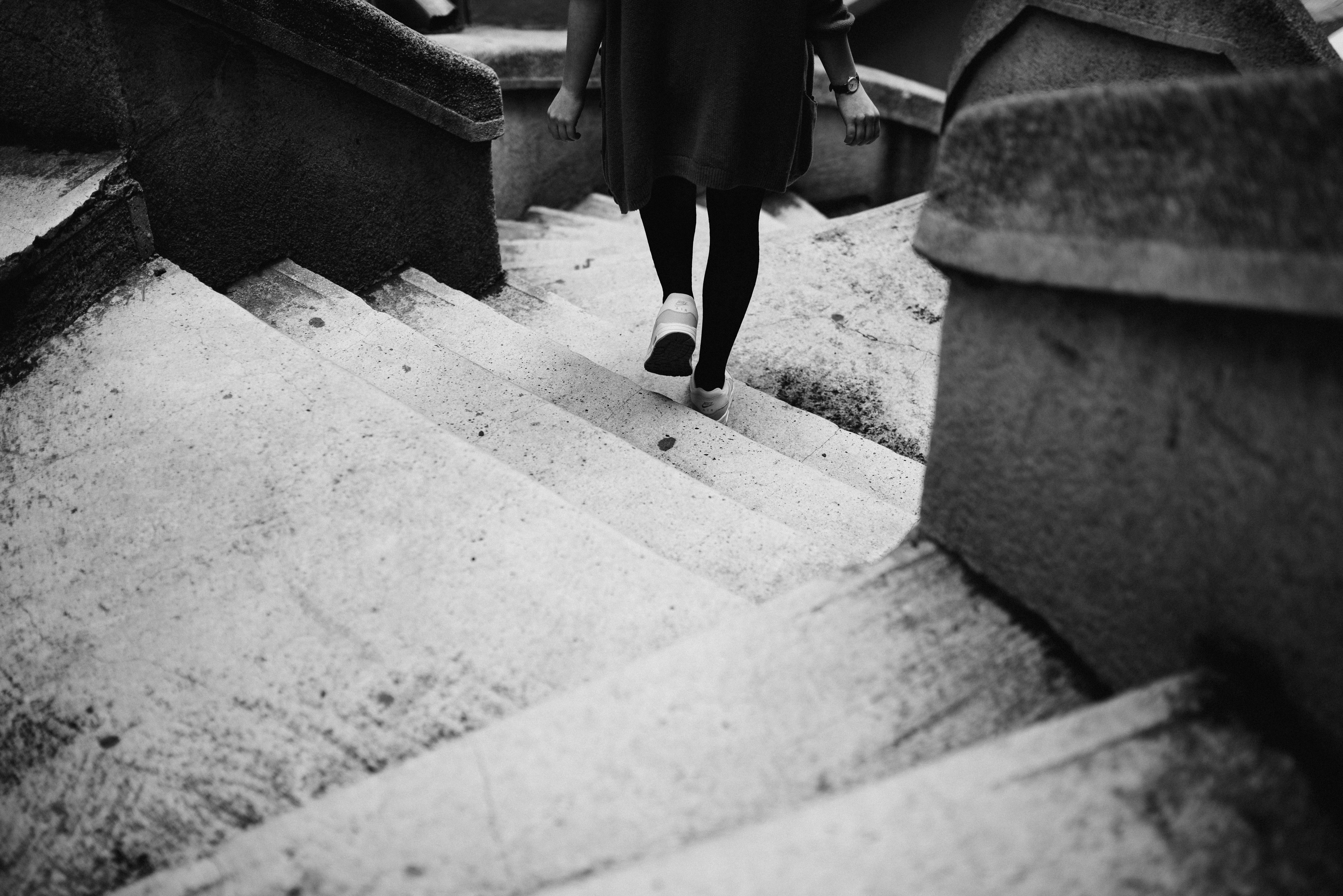 Black and white shot of person in cardigan and tights walking down stairs at Galata Tower