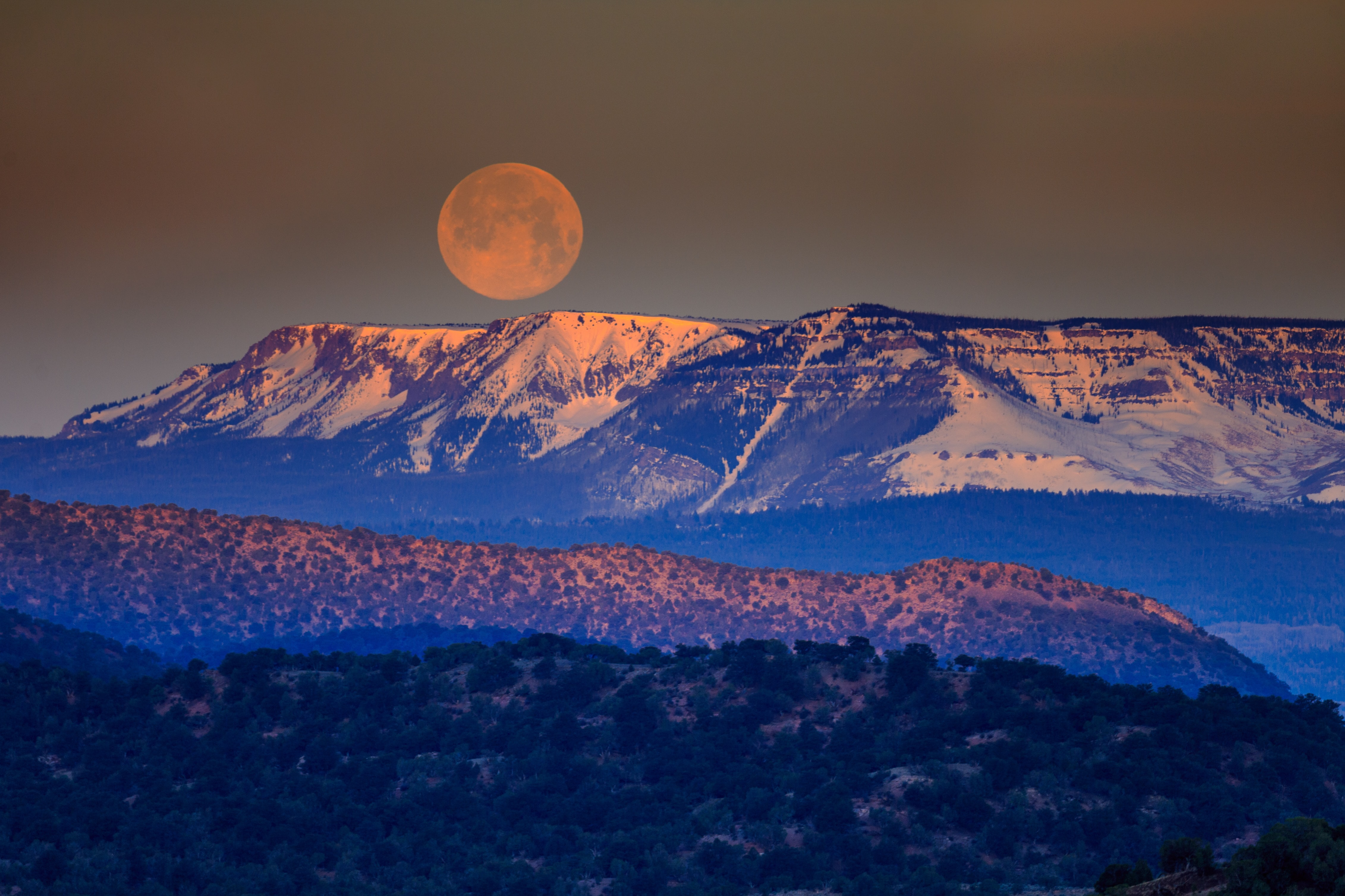 A large full moon over table-top mountains at dusk