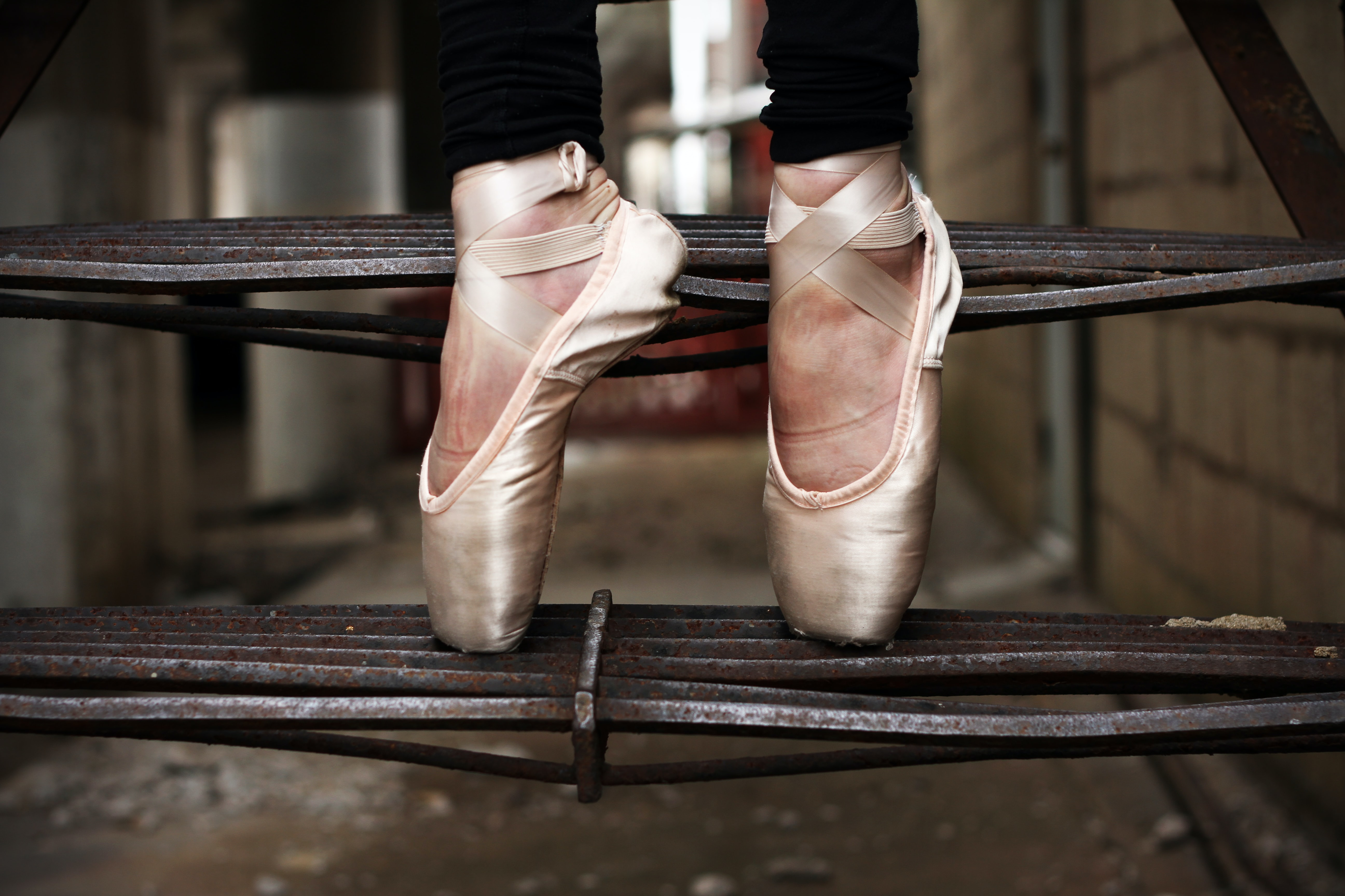 A woman standing on her tippy-toes in dance shoes on an outdoor staircase.