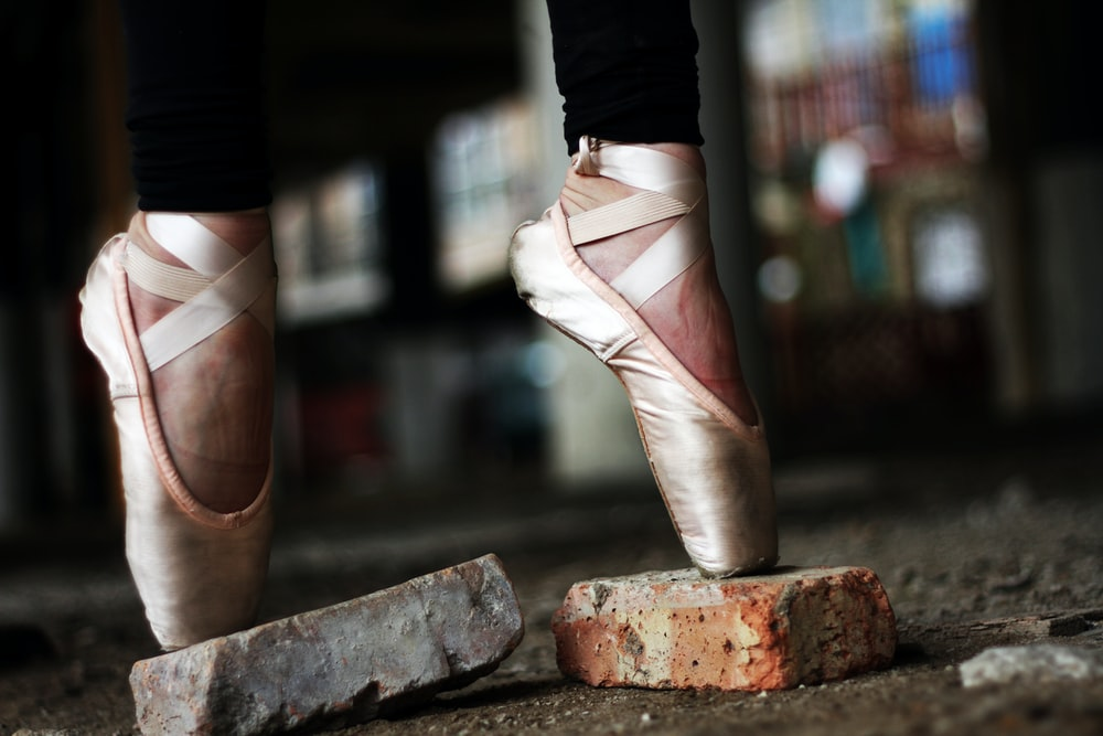 person wearing gold ballerina shoes