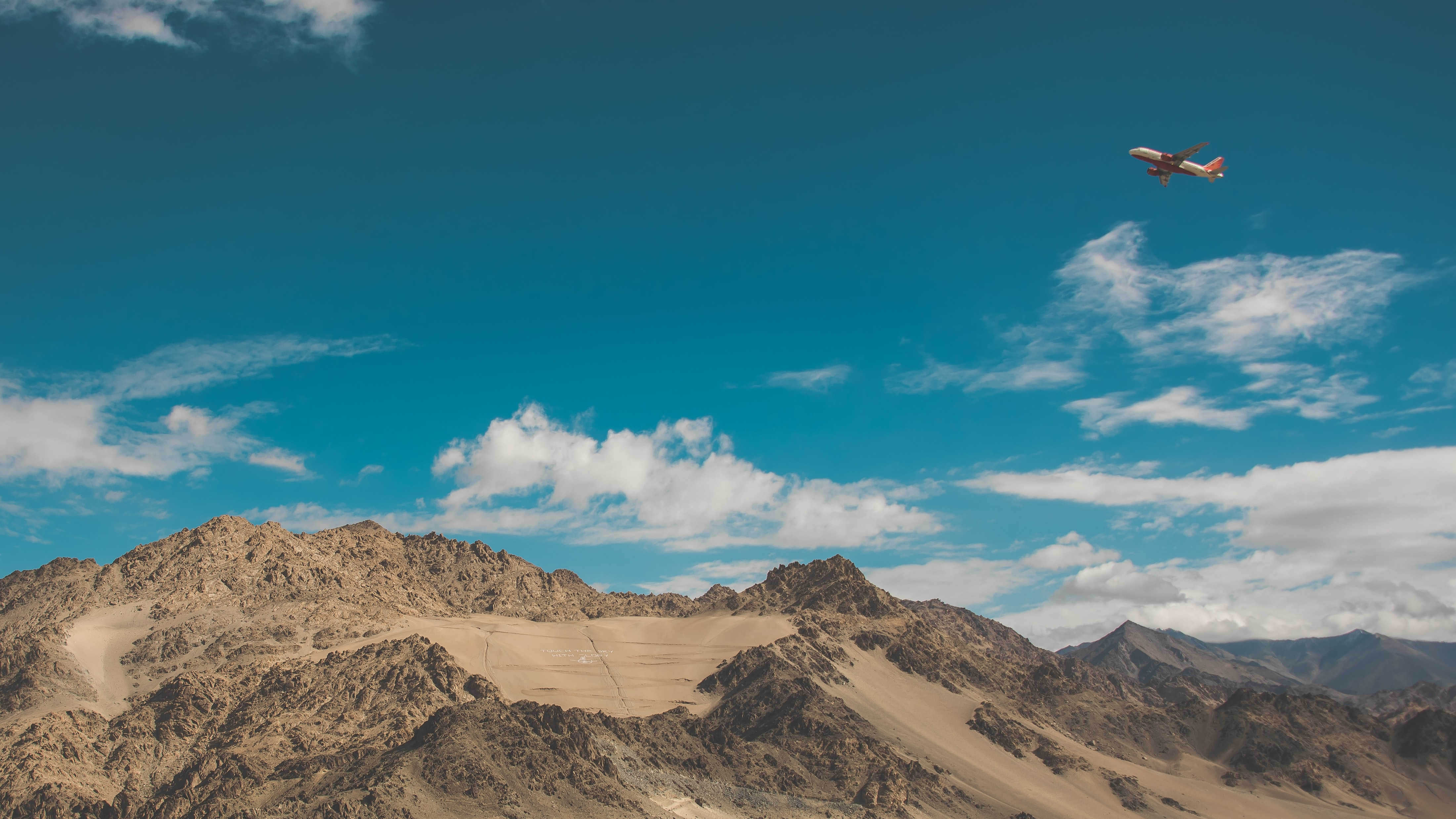 An airplane in the sky over mountains in Northern India