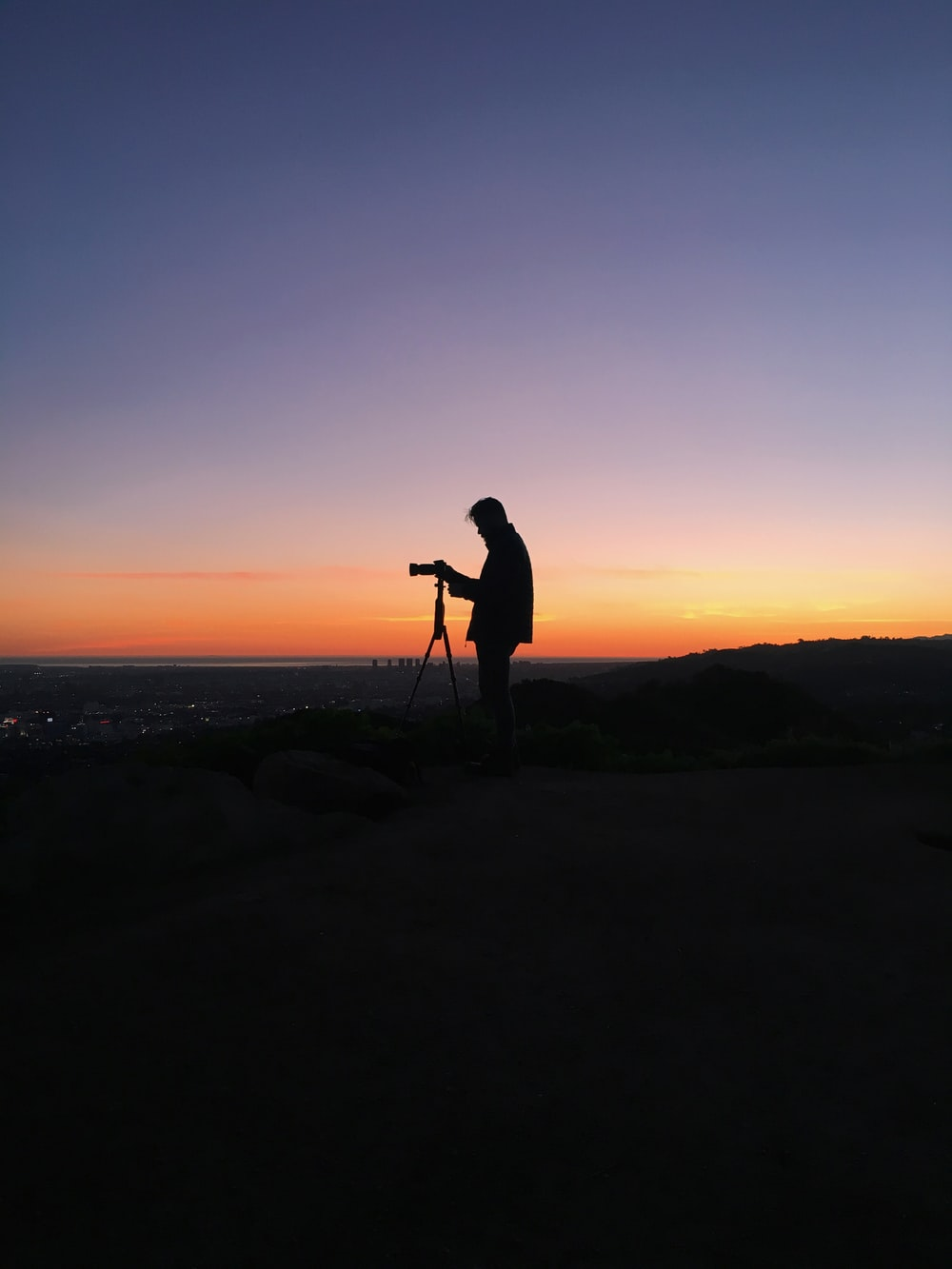 silhouette of man in front of DSLR camera during golden hour