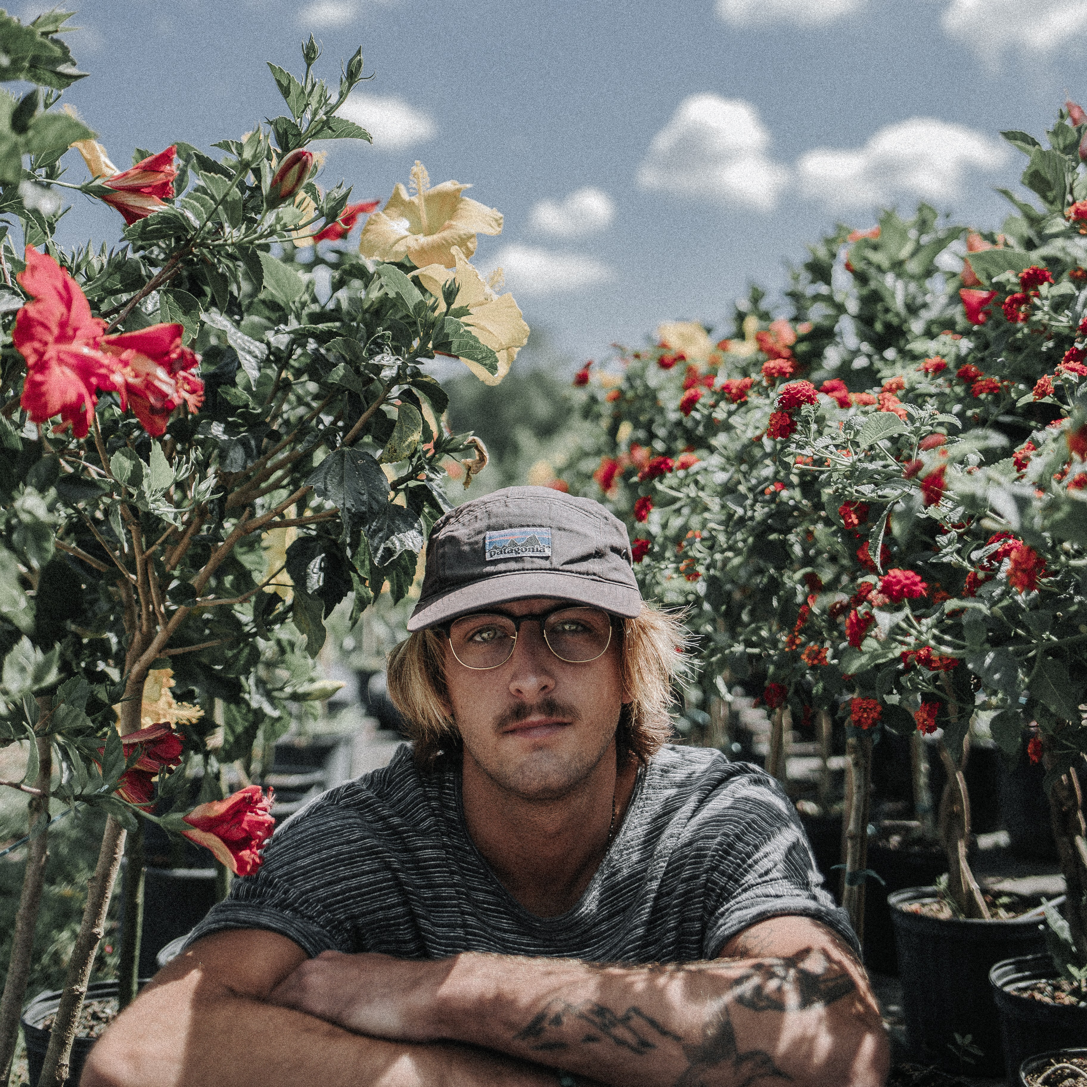 Man in a Patagonia hat and tattoos sitting by rows of flower bushes