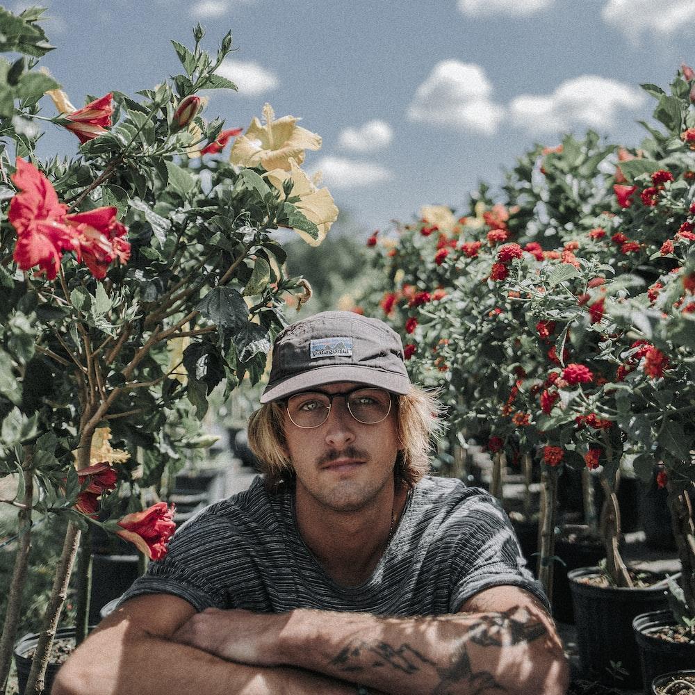 man sitting near hibiscus flowers during daytime