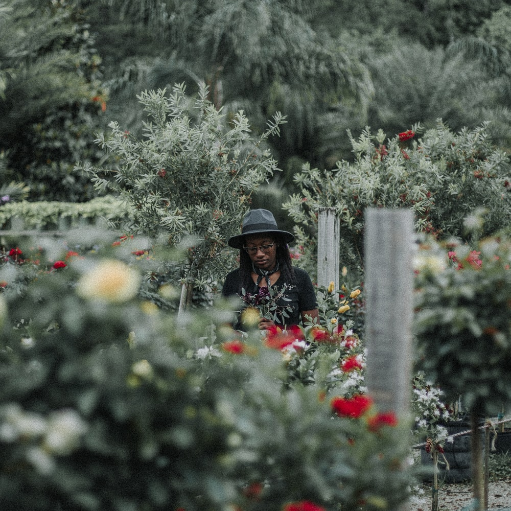 woman in black hat standing on garden