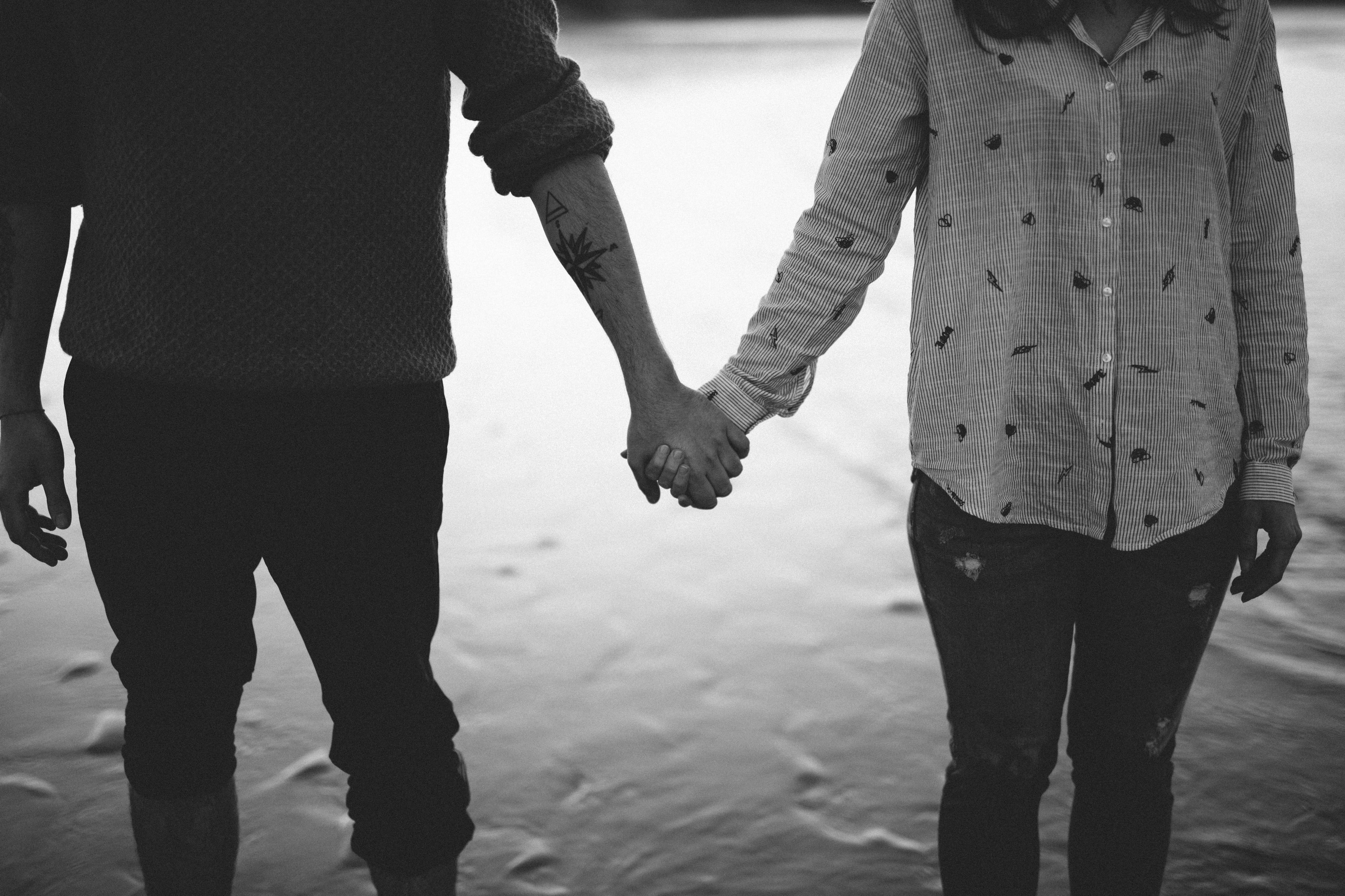 man and woman holding hands standing on body of water