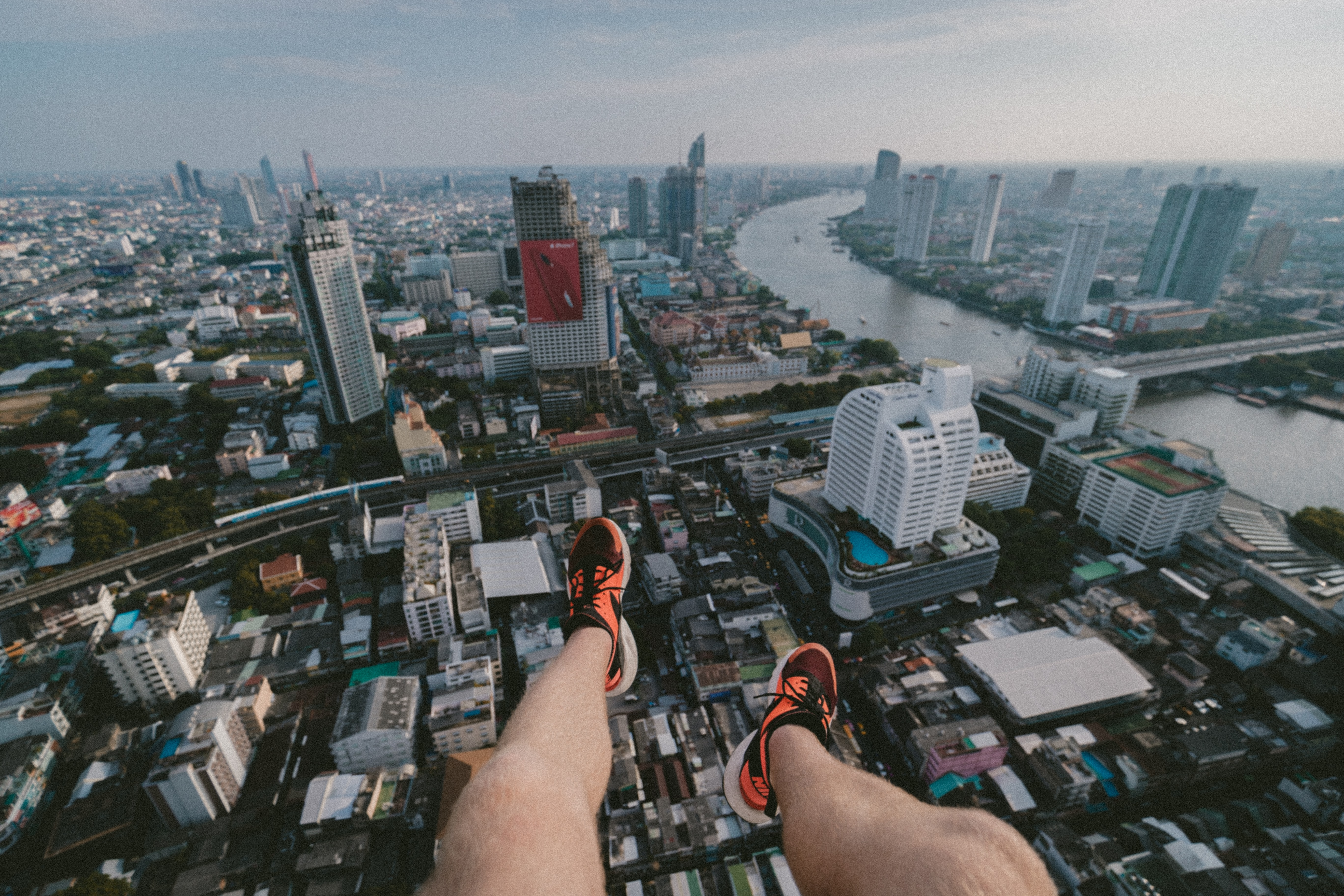 man paragliding taking aerial photography of city scapes during daytime