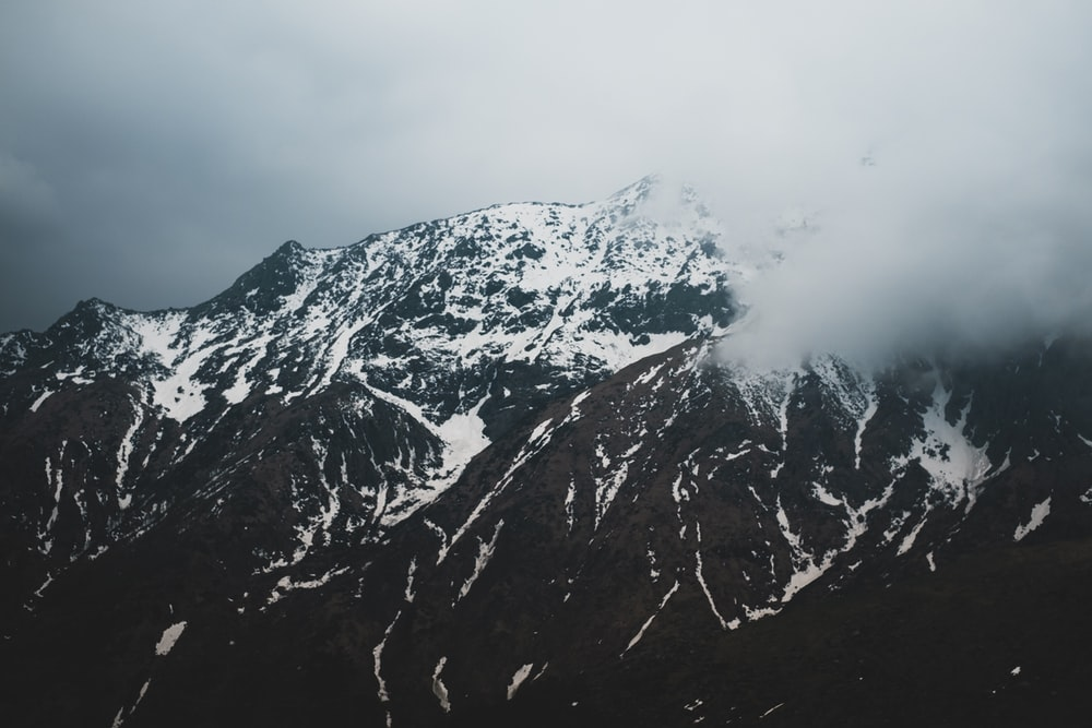 mountain covered with snow and surrounded with clouds
