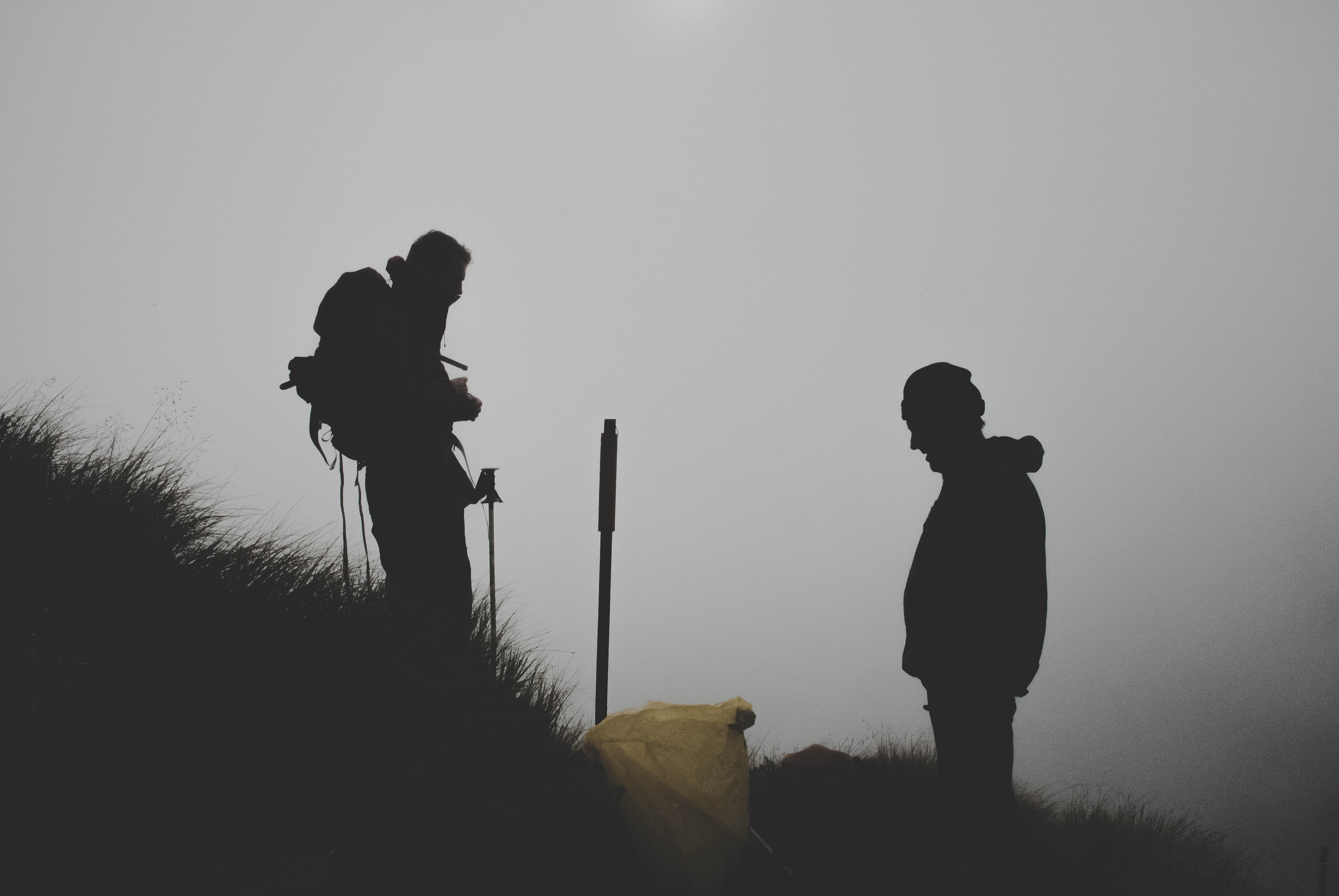 Silhouette of two hikers on a slope against the gray background in Mount Aspiring National Park.