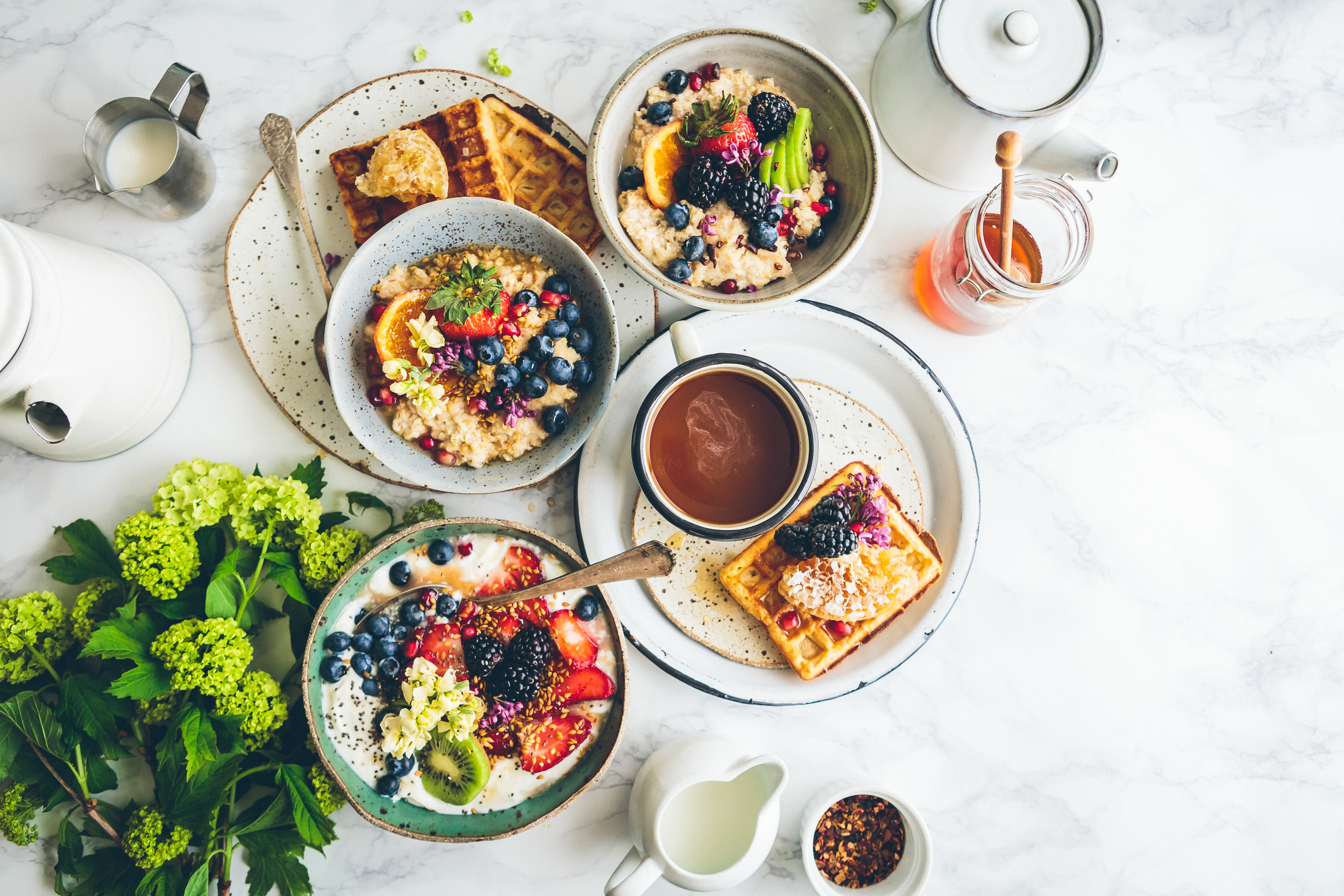 An overhead shot of a waffle, bowls of fruit oatmeal and a cup of coffee