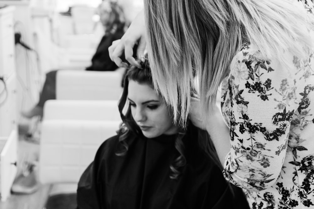 grayscale photography of woman getting her hair done inside salon